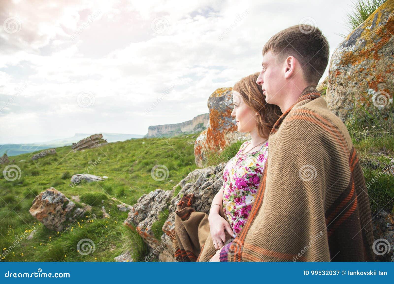 Retrato de un individuo con una muchacha cubierta en una manta que se coloca en un abrazo en naturaleza y que sonríe con felicida