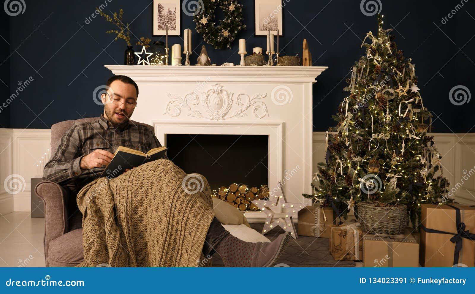 Retrato de un libro de lectura del hombre a la cámara el la tarde de la Navidad