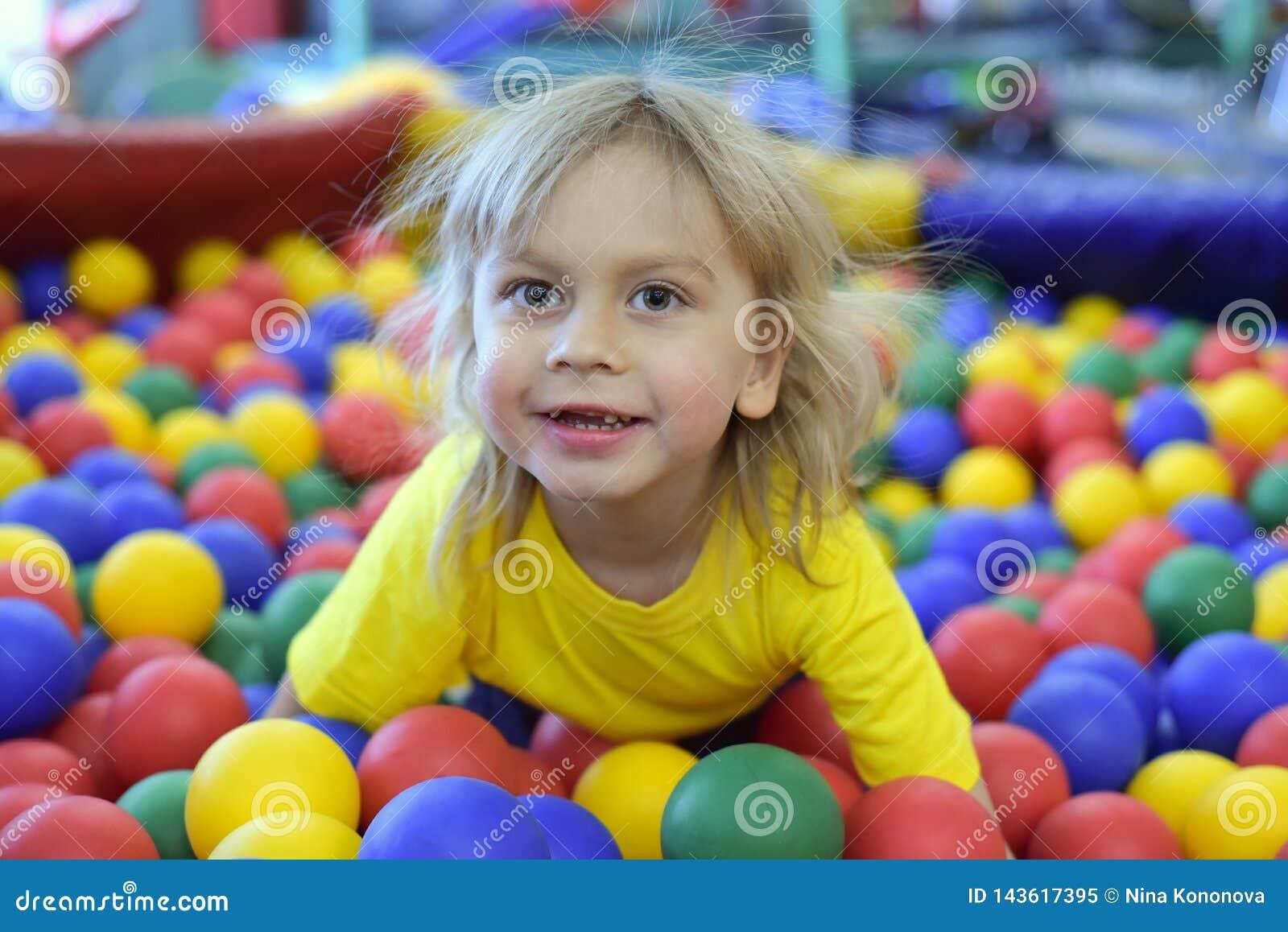 Retrato de un muchacho rubio en una camiseta amarilla Las sonrisas y los juegos del niño en la sala de juegos de los niños Piscin