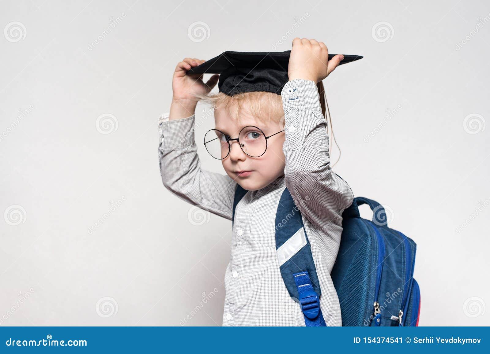 Retrato de un muchacho rubio en vidrios, un sombrero académico y una cartera en un fondo blanco Concepto de la escuela