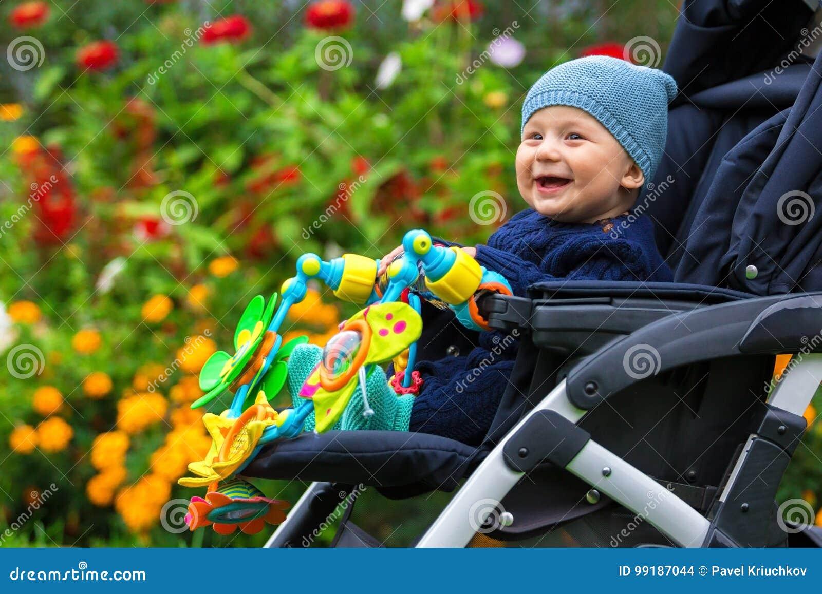 Retrato de un niño feliz en un carro de bebé al aire libre