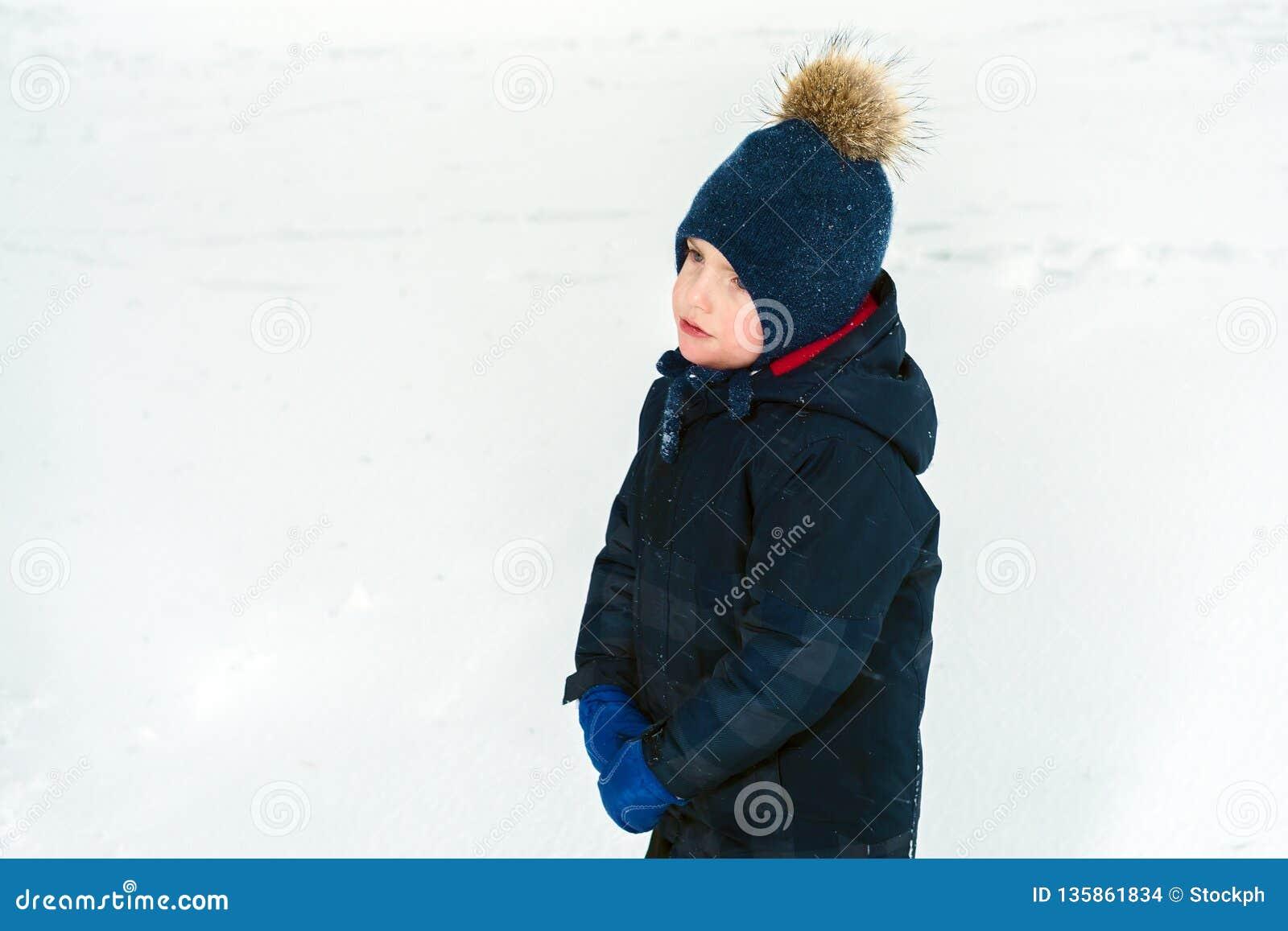 Retrato de un niño pequeño triste el niño ofendido está llorando en una carpeta y una chaqueta azules, manoplas que llevan en