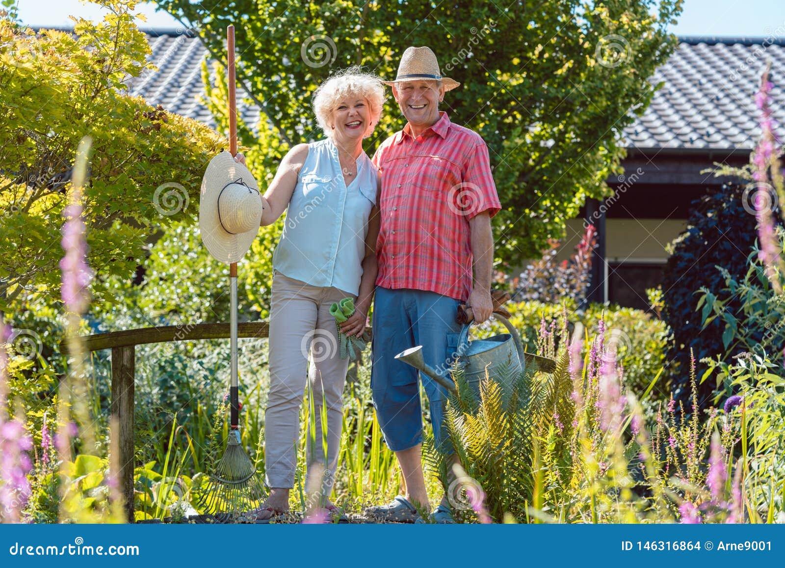 Retrato de un par mayor activo que sostiene las herramientas que cultivan un huerto en el jardín