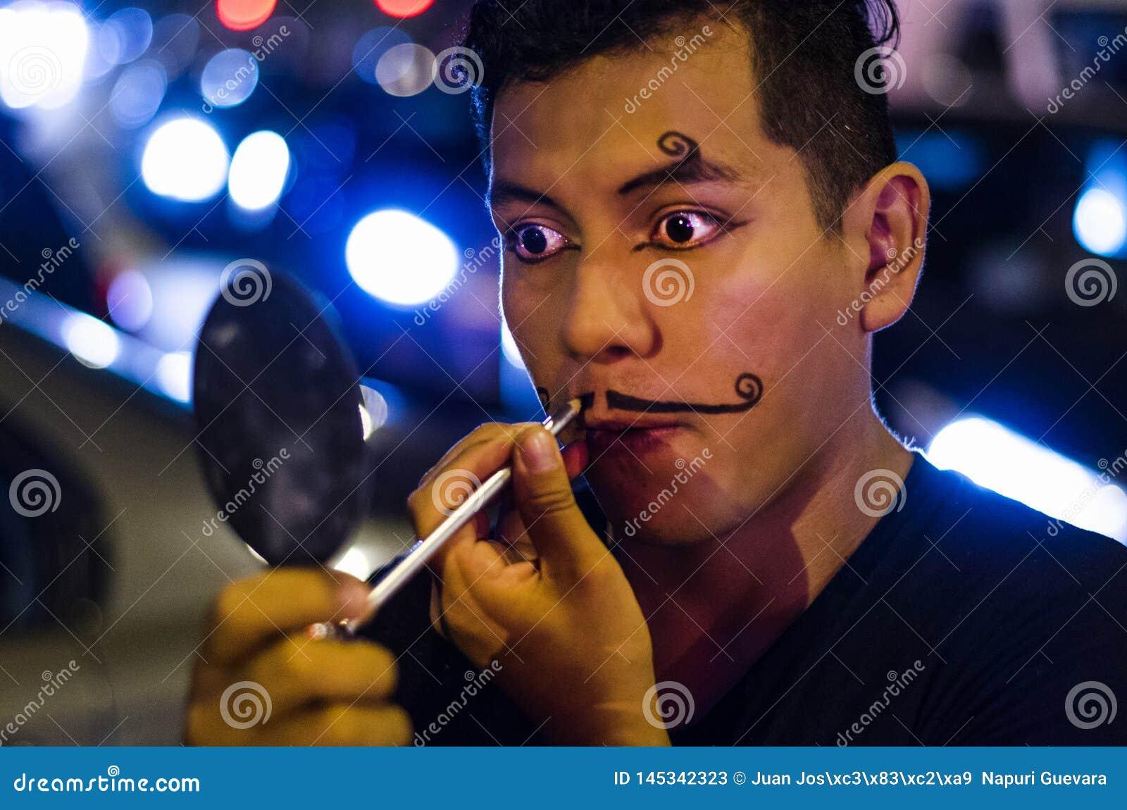 Retrato de un payaso joven que pone en los bigotes con maquillaje