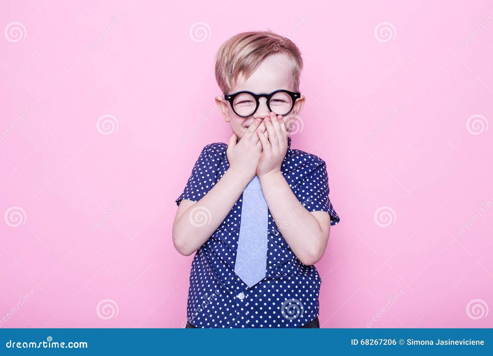 Retrato de un pequeño muchacho sonriente en vidrios y un lazo divertidos Escuela pre-entrenamiento Moda Retrato del estudio sobre