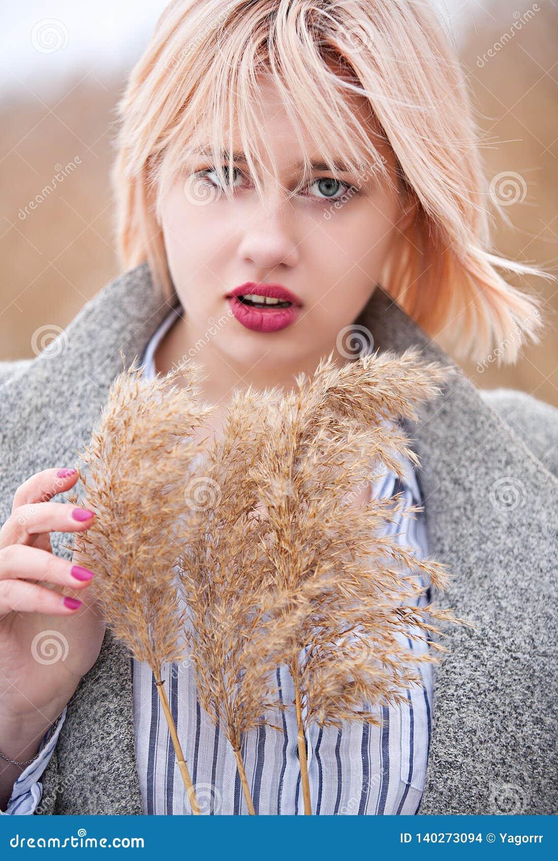 Retrato de un rubio hermoso joven con los tallos de lámina en sus manos