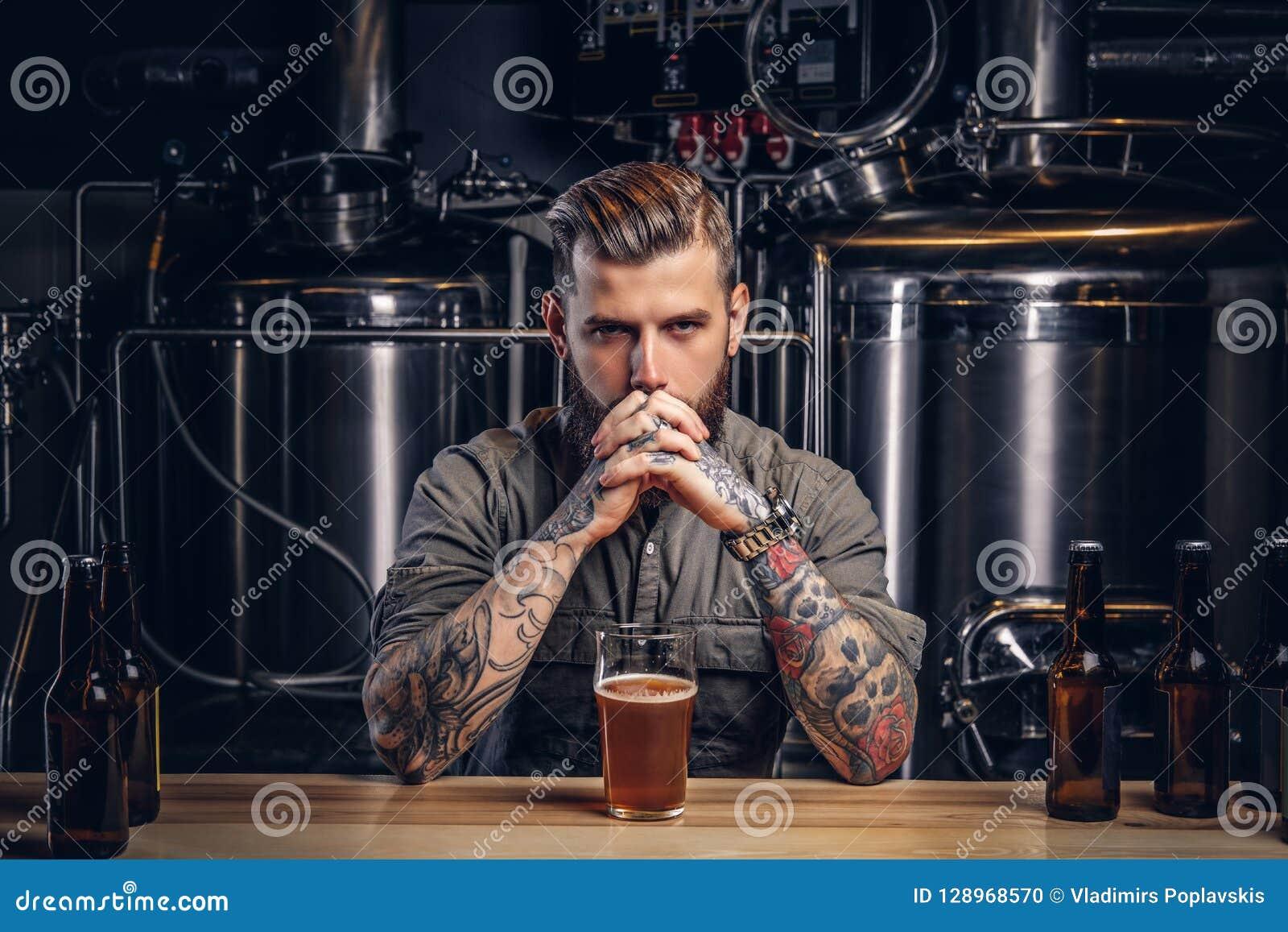 Retrato de un varón tatuado pensativo del inconformista con la barba elegante y del pelo en la camisa en cervecería del indie