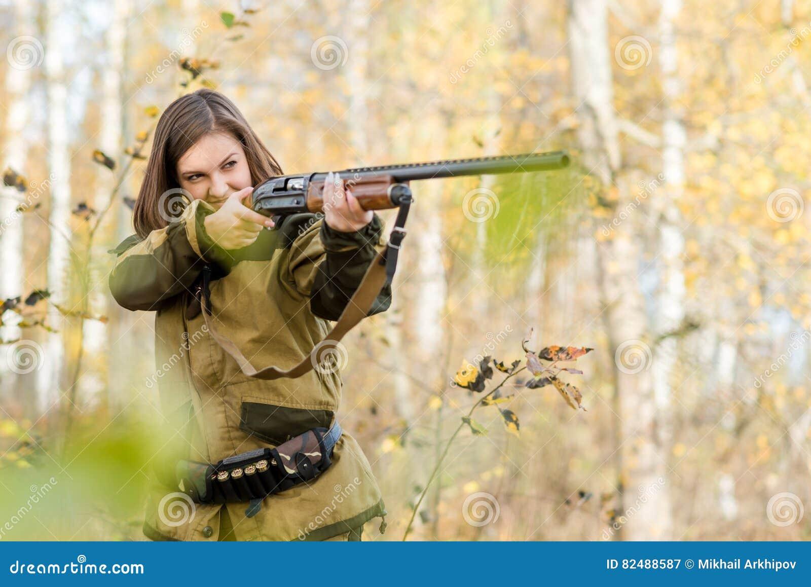 Retrato de una chica joven hermosa en cazador del camuflaje con la escopeta