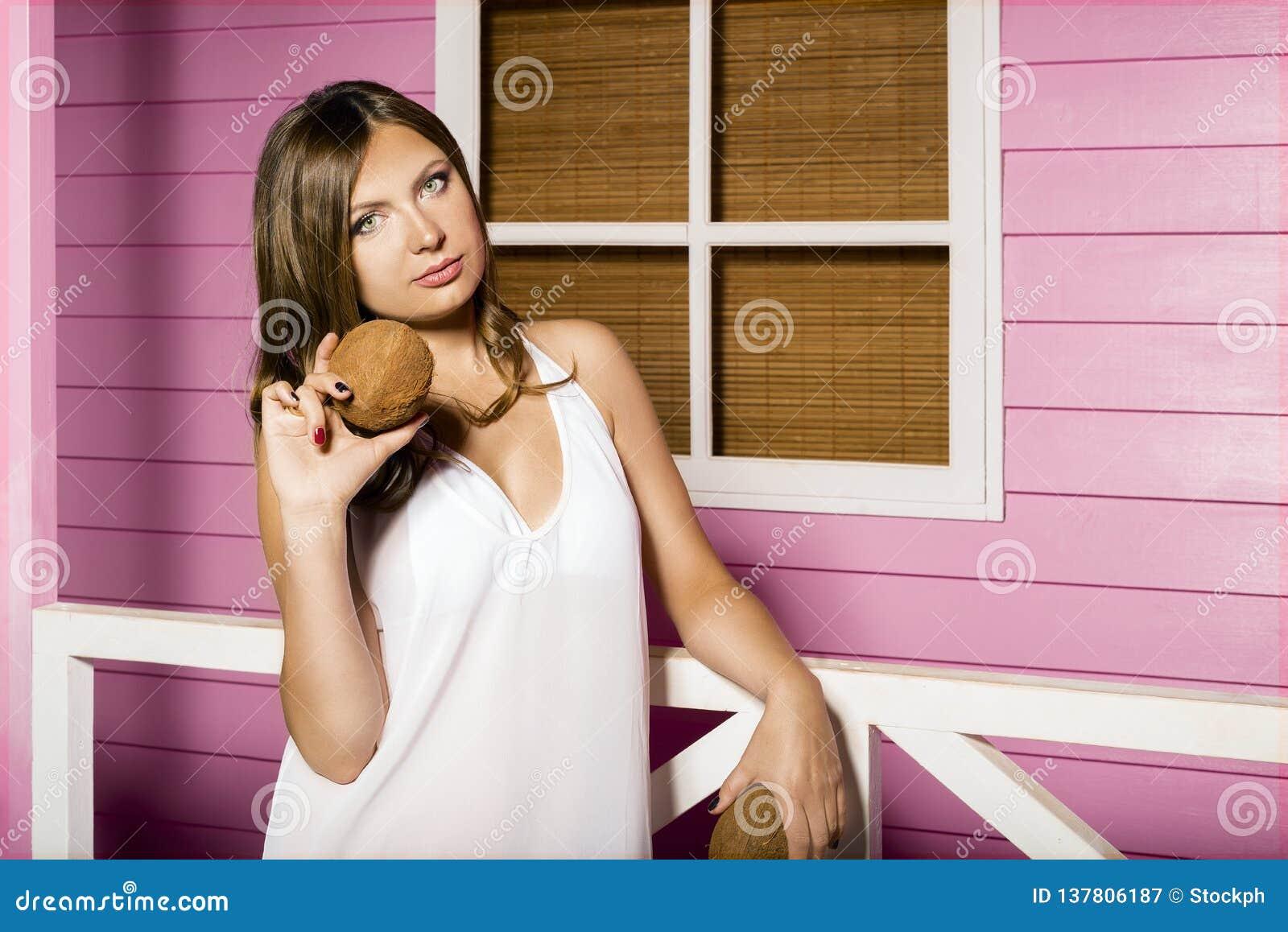 Retrato de una chica joven hermosa la mujer atractiva se coloca cerca de la casa del rosa de la playa y sostiene los cocos en su