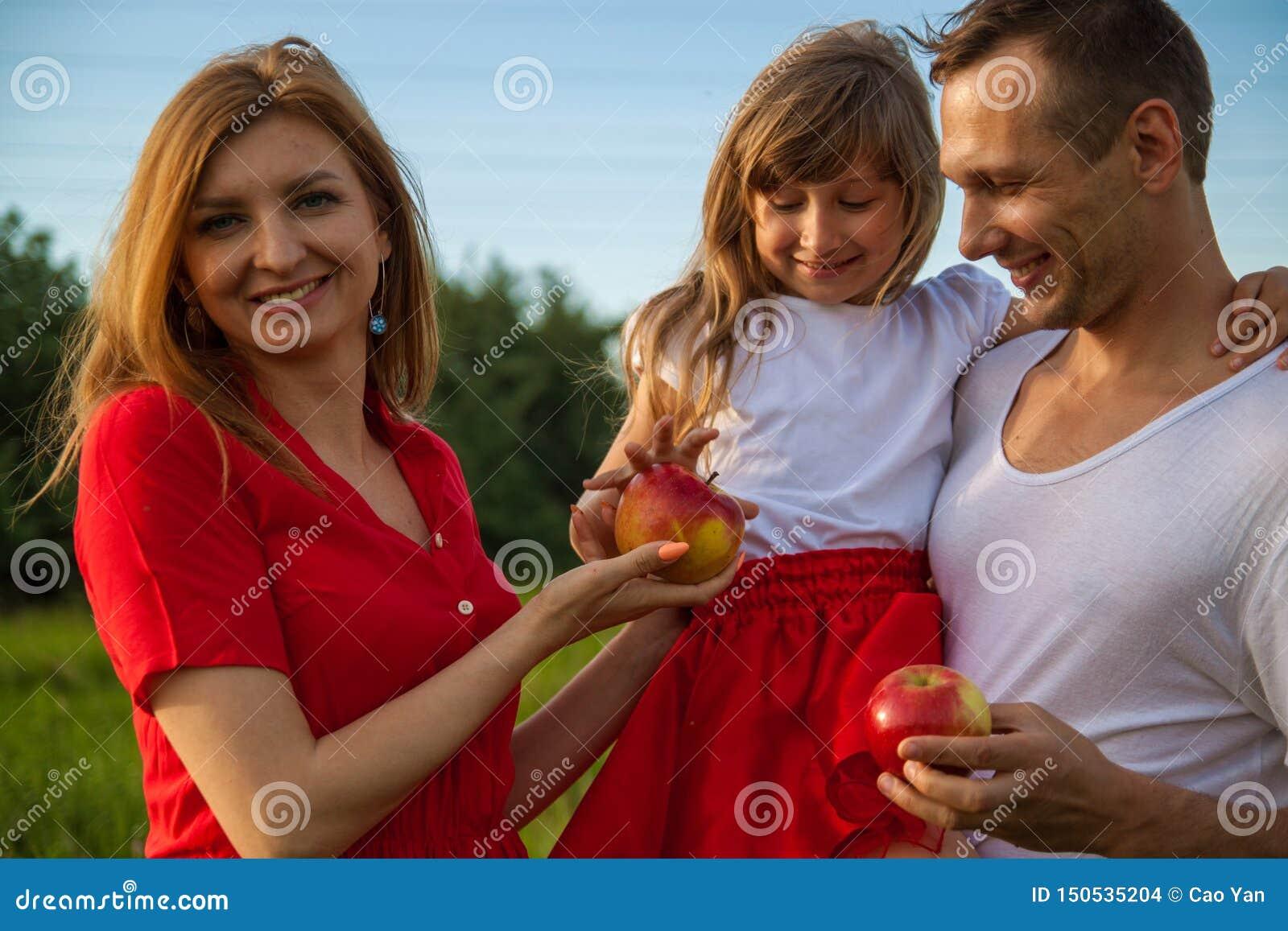 Retrato de una familia europea de tres La familia feliz joven con un pequeño niño en naturaleza está sonriendo