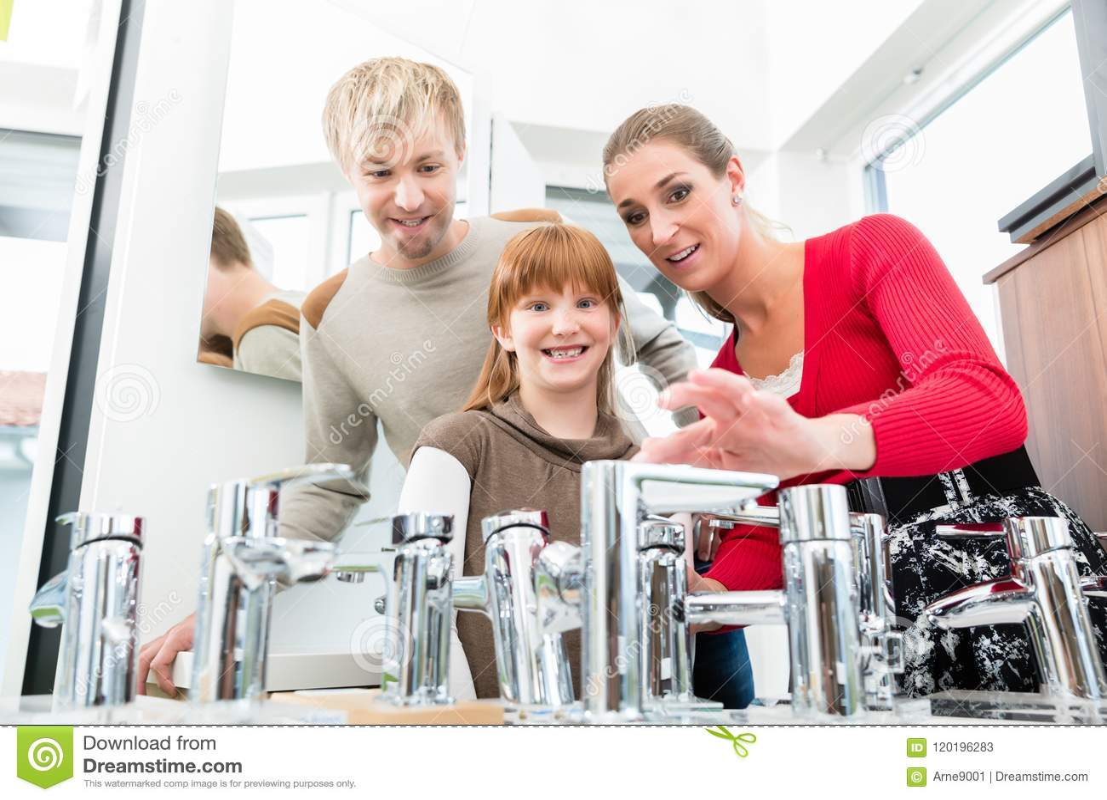 Retrato de una familia feliz que busca un nuevo grifo del fregadero del cuarto de baño