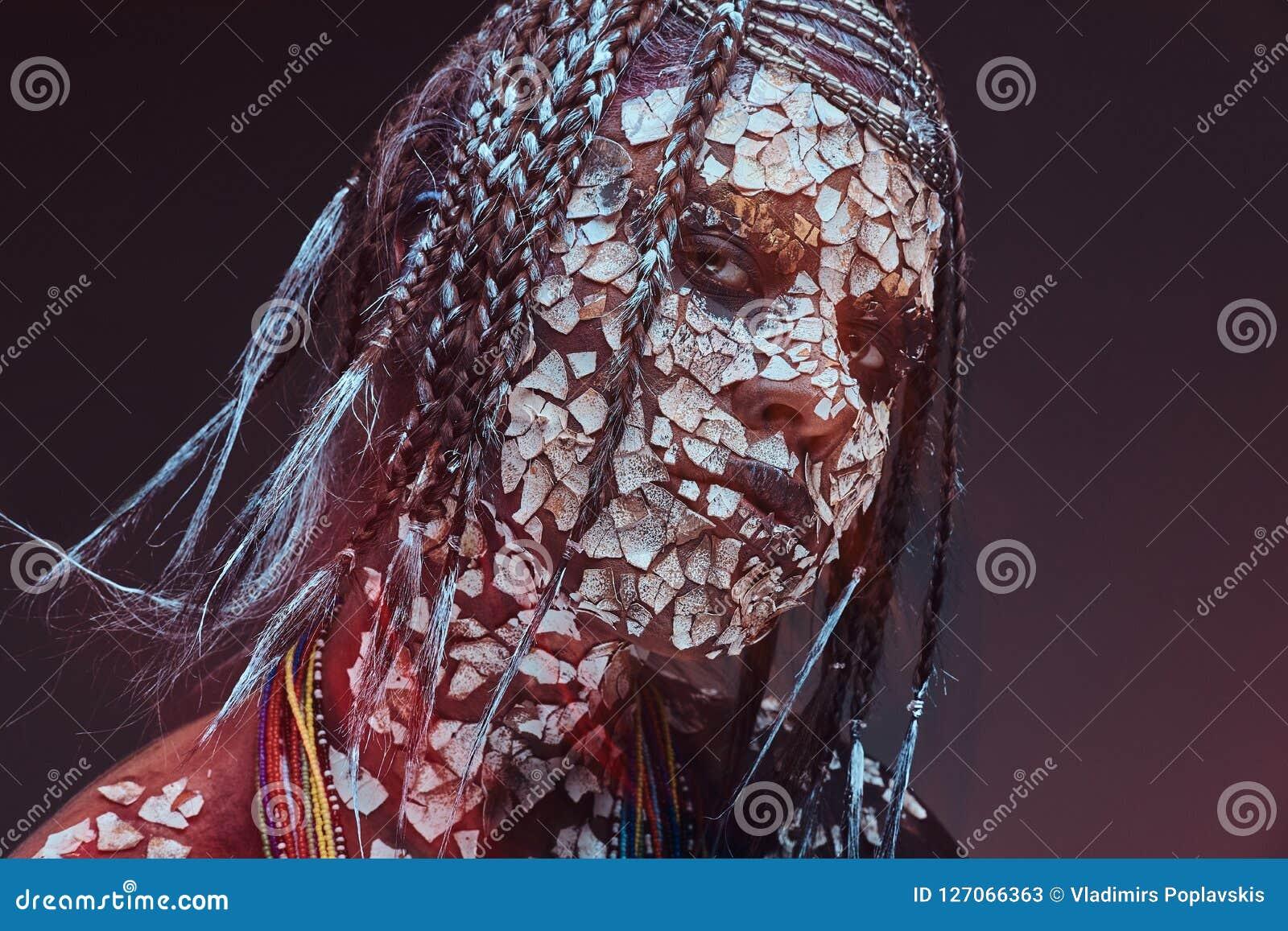 Retrato de una hembra africana asustadiza del chamán con una piel agrietada aterrorizada y dreadlocks Concepto del maquillaje