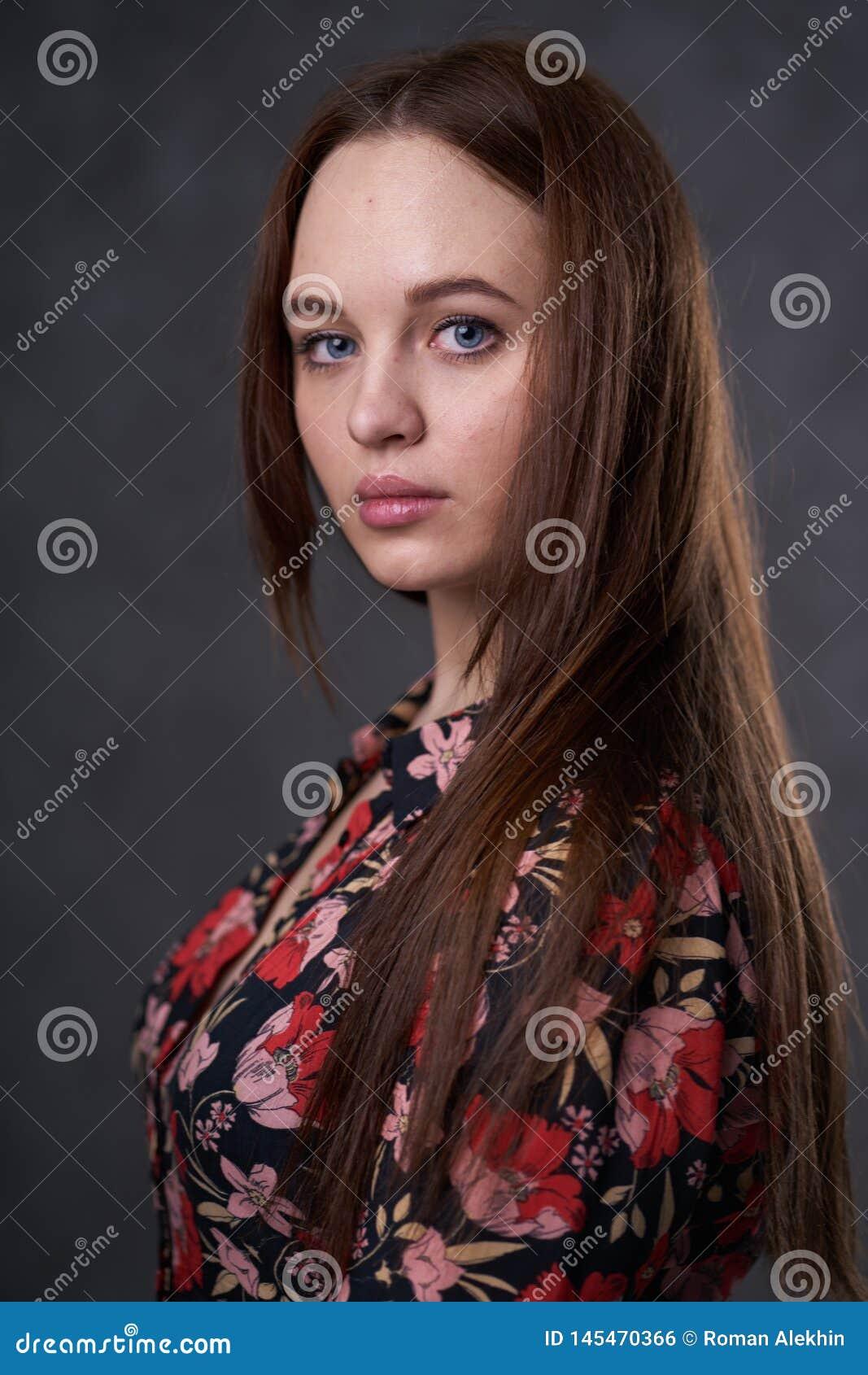 Retrato de una hembra en un vestido coloreado en fondo gris