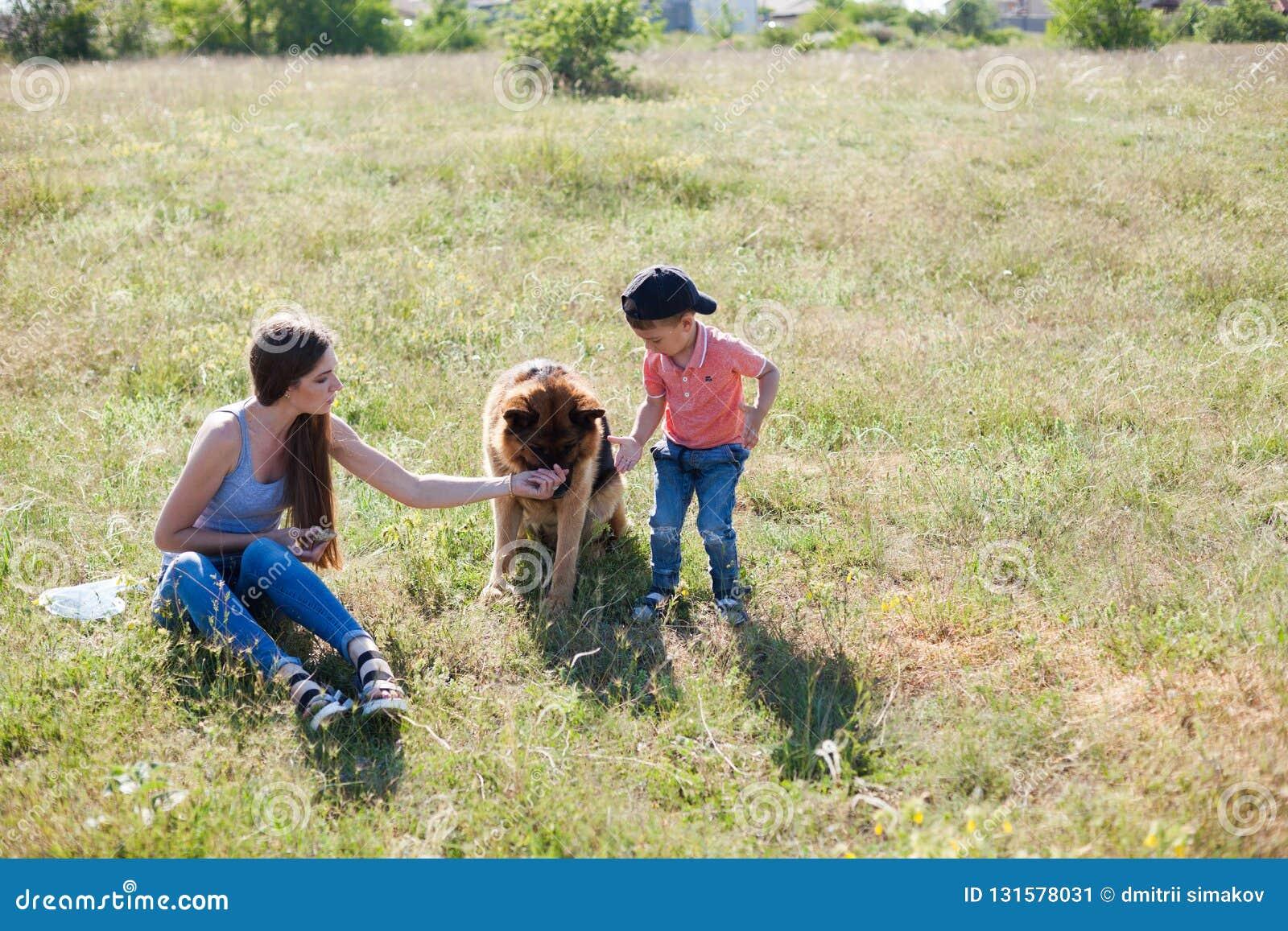Retrato de una madre con un hijo y un perro jovenes