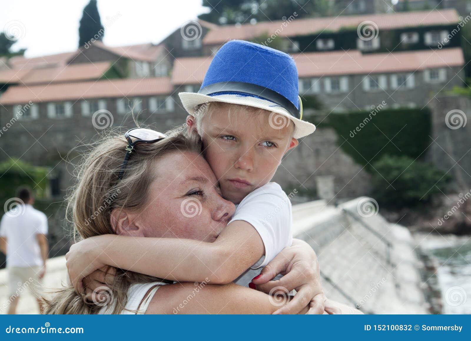 Retrato de una madre joven que abraza a su ni?o el vacaciones en