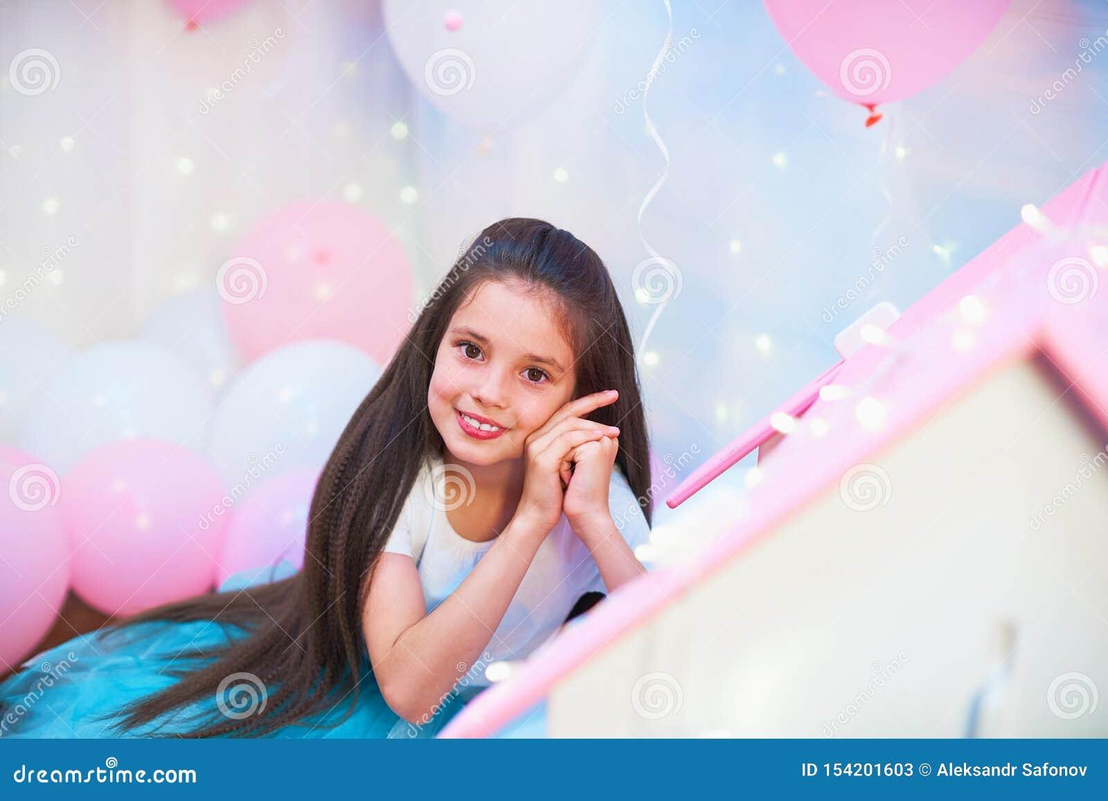 Retrato de una muchacha adolescente hermosa en una falda multicolora enorme del tutú en un paisaje del globo los globos de la hoj
