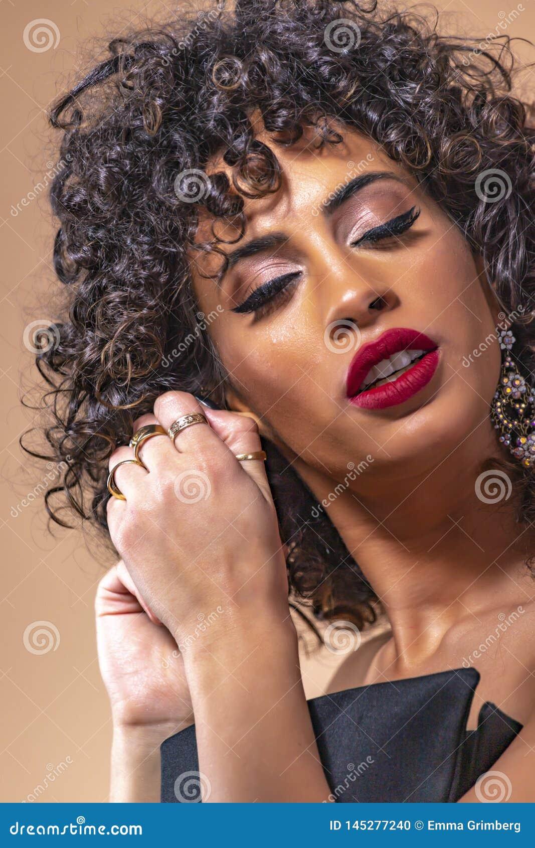 Retrato de una muchacha con el pelo rizado negro con maquillaje en pendientes que llevan de un vestido de noche cerca para arriba