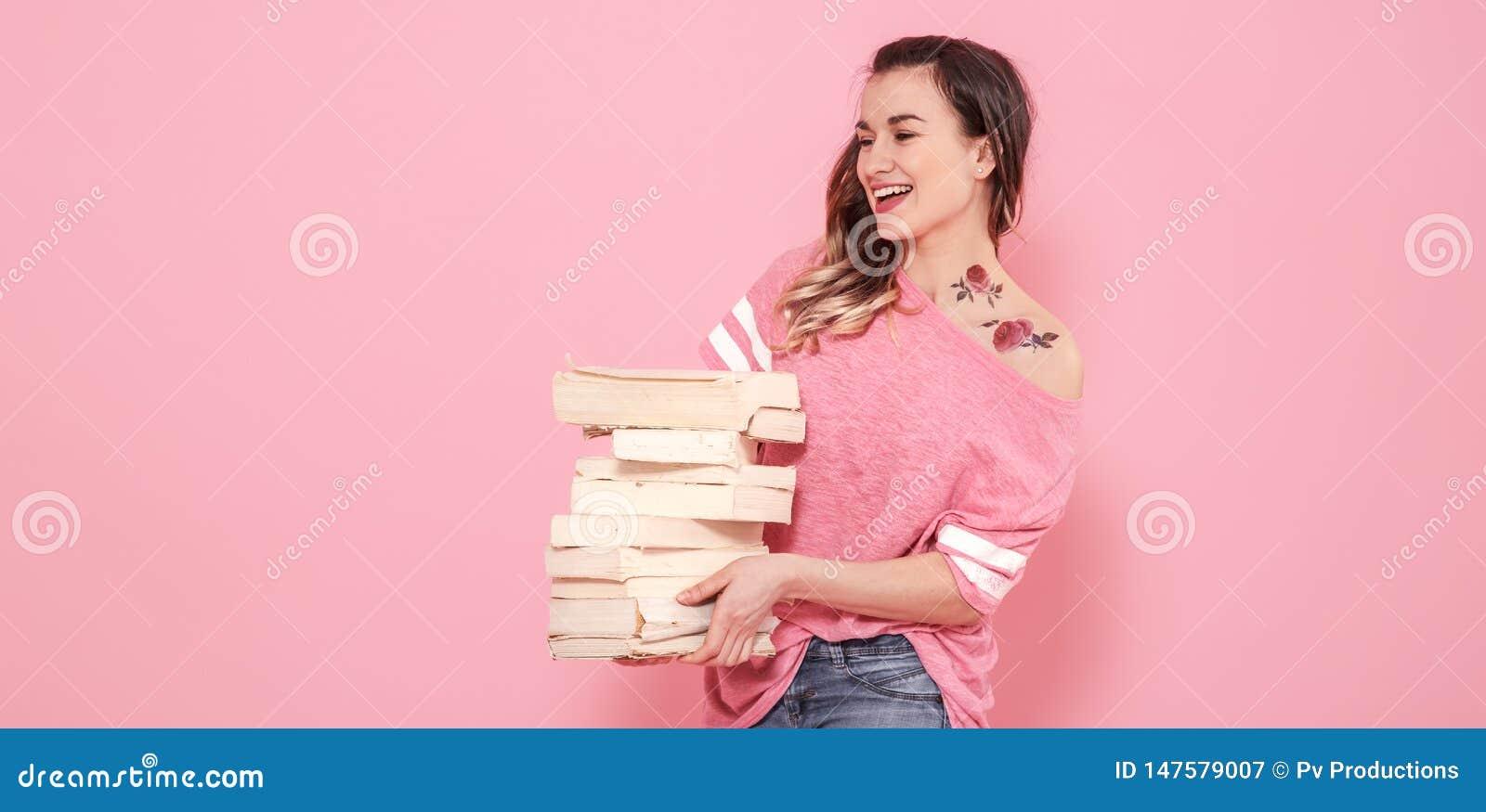Retrato de una muchacha con una pila de libros en un fondo rosado