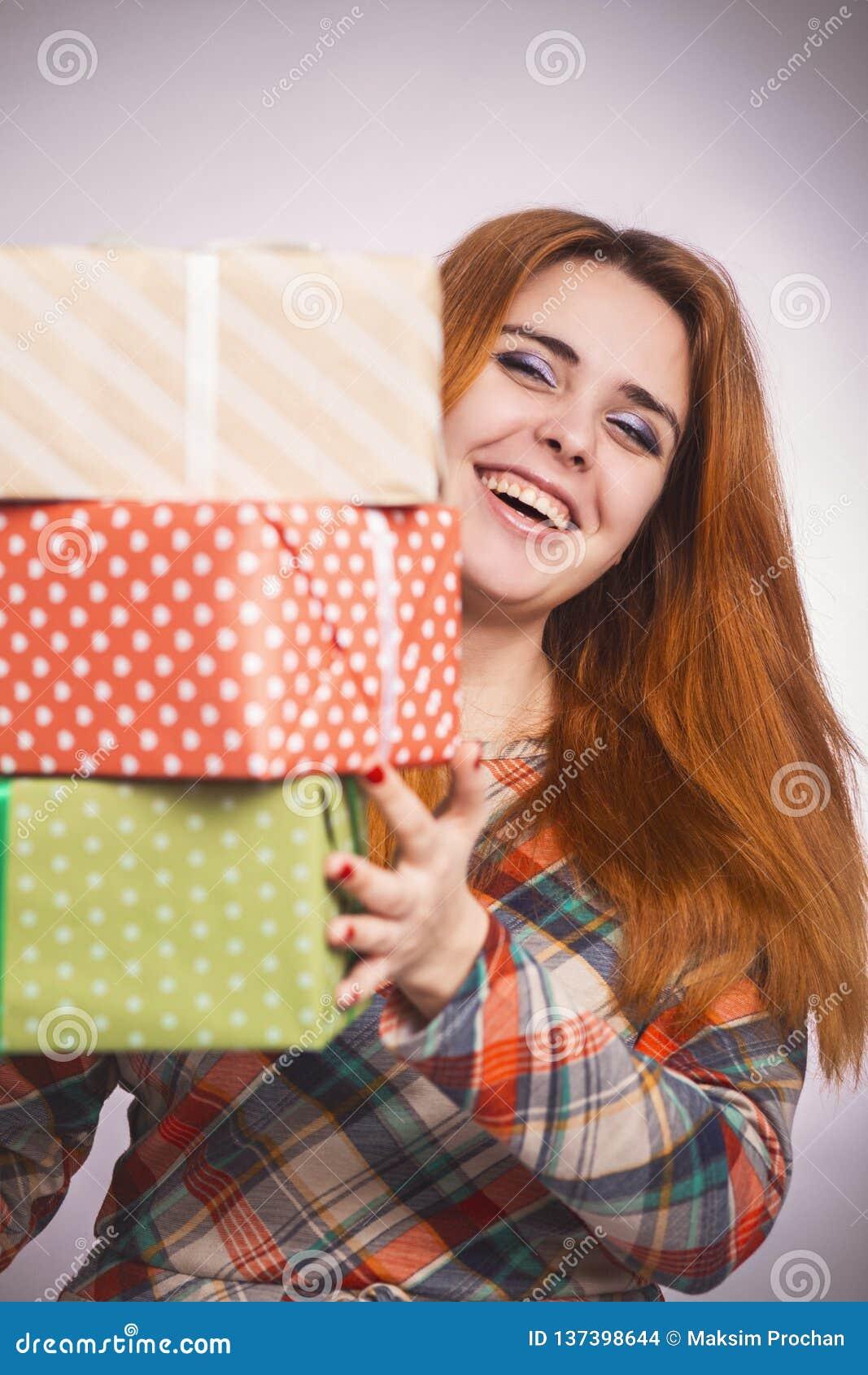 Retrato de una muchacha feliz hermosa con las porciones de regalos en manos, mujer joven que sostiene una pila de cajas envueltas