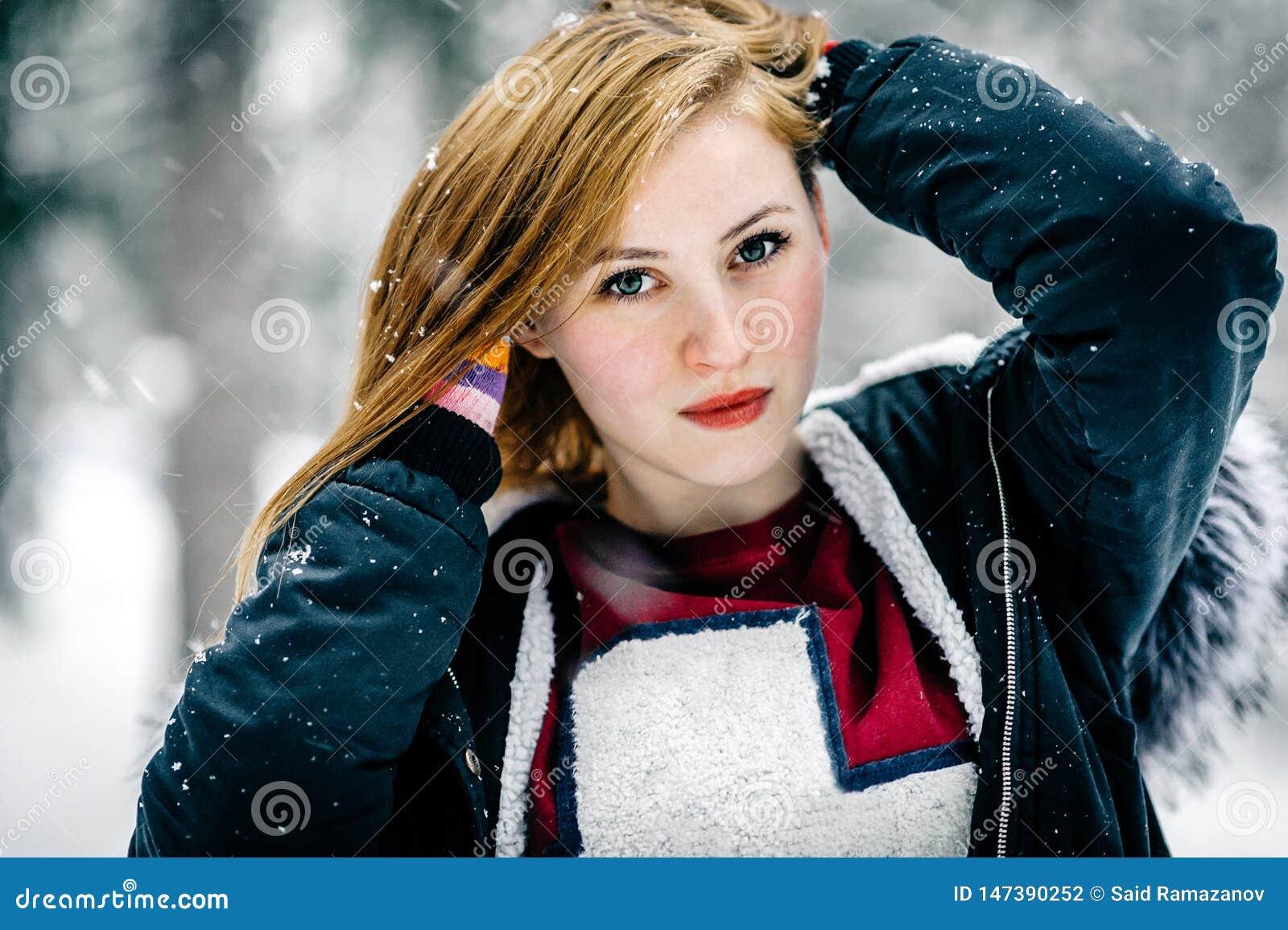 Retrato de una muchacha hermosa en la chaqueta negra con la capilla de la piel en medio del bosque del invierno