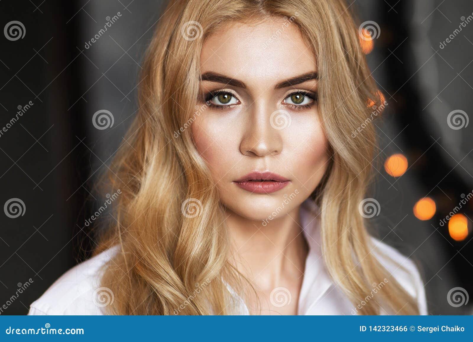 Retrato de una muchacha hermosa joven en una camisa blanca que mira en la cámara