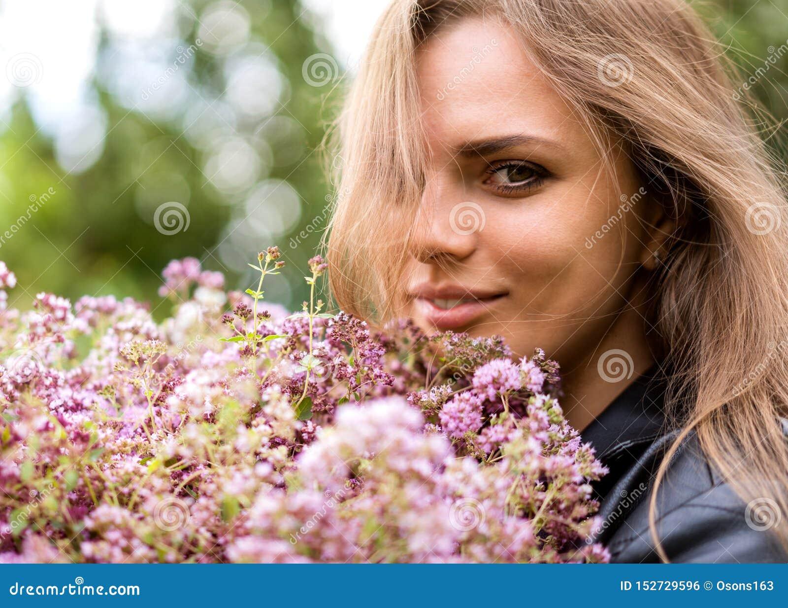 Retrato de una muchacha hermosa de la moda con un ramo de flores de la lila en la calle