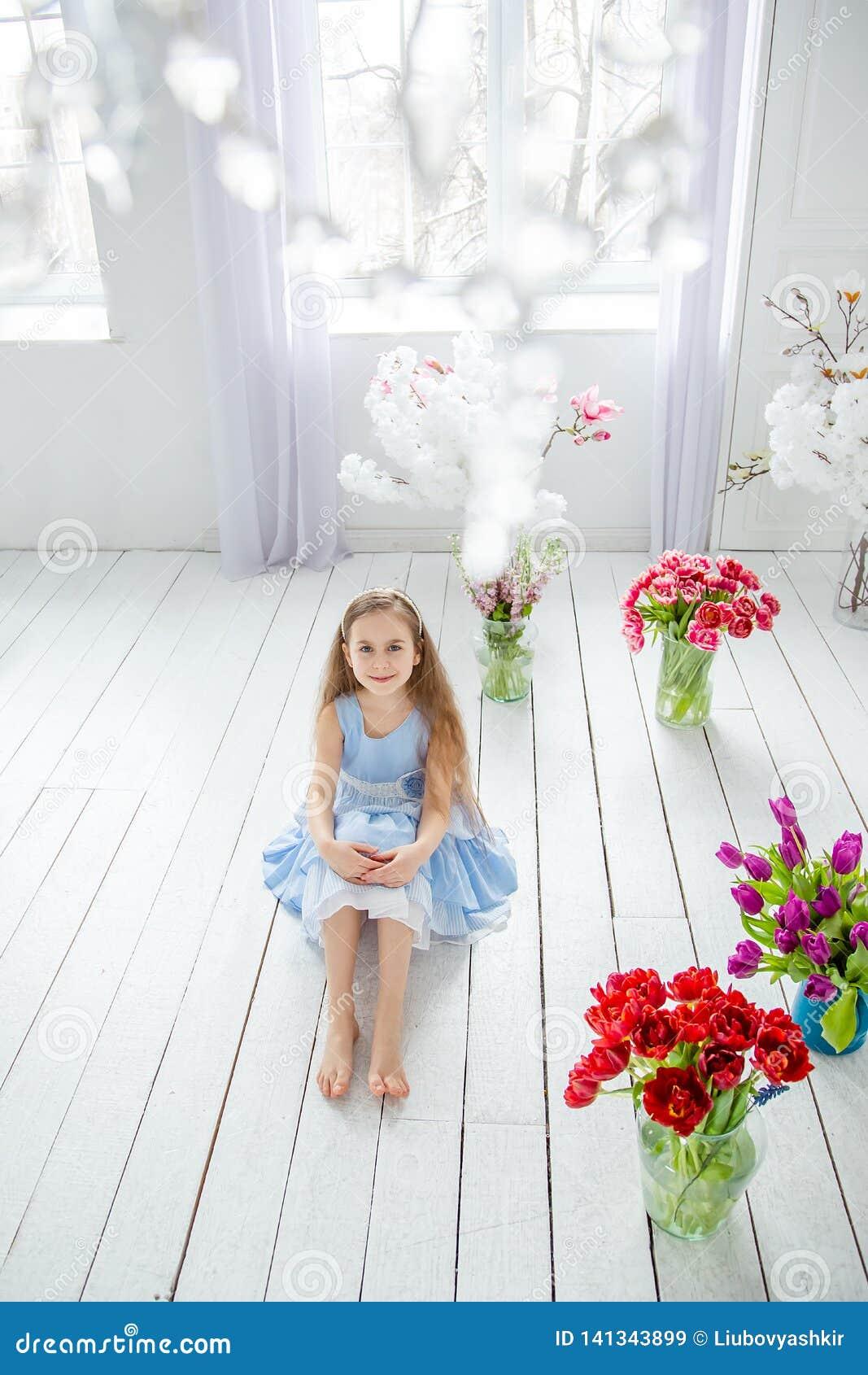 Retrato de una muchacha de ojos azules hermosa, niña entre las flores de la primavera en un cuarto brillante