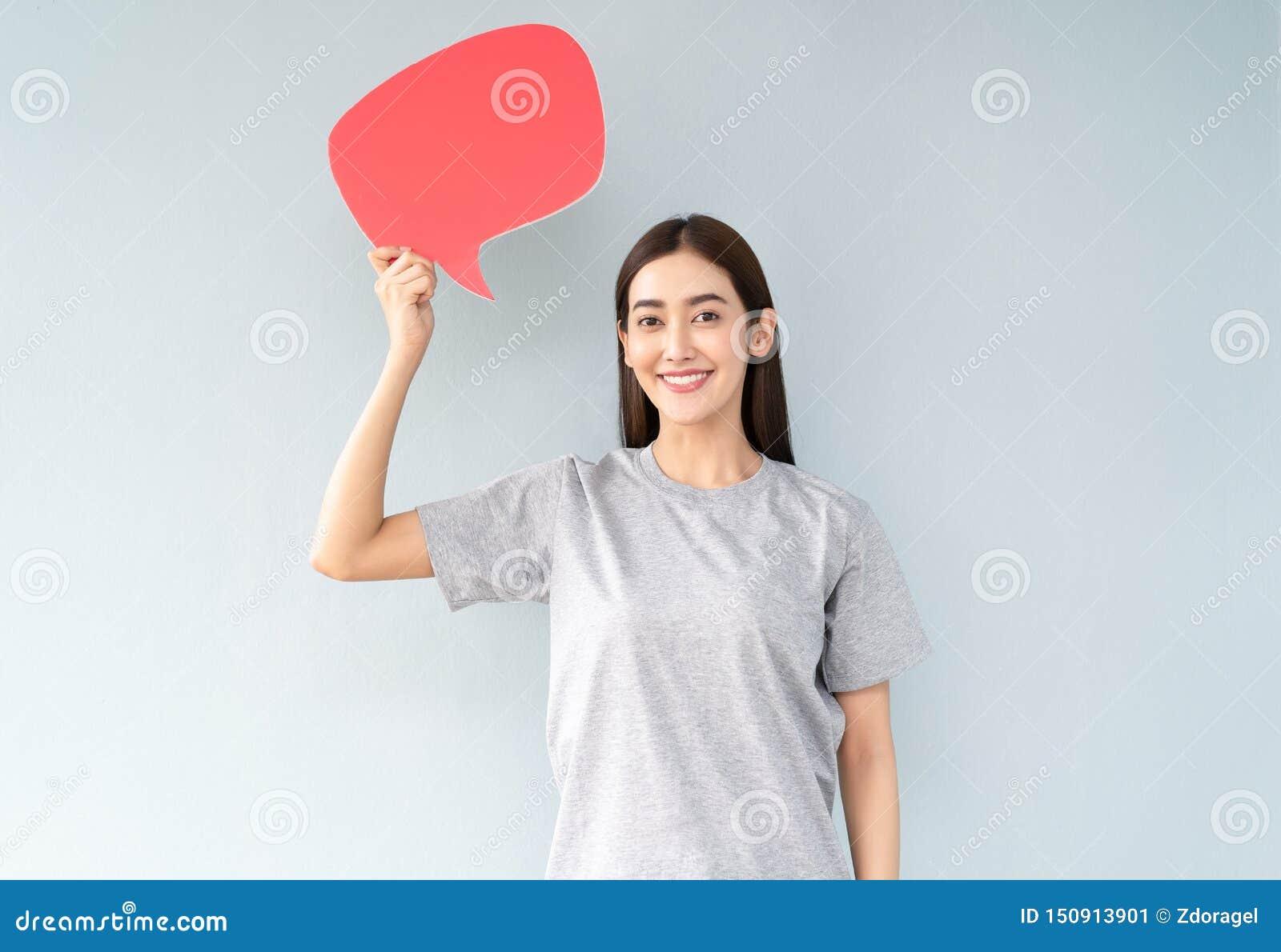 Retrato de una mujer asiática joven feliz mientras que soporta iconos de la burbuja del discurso sobre fondo gris