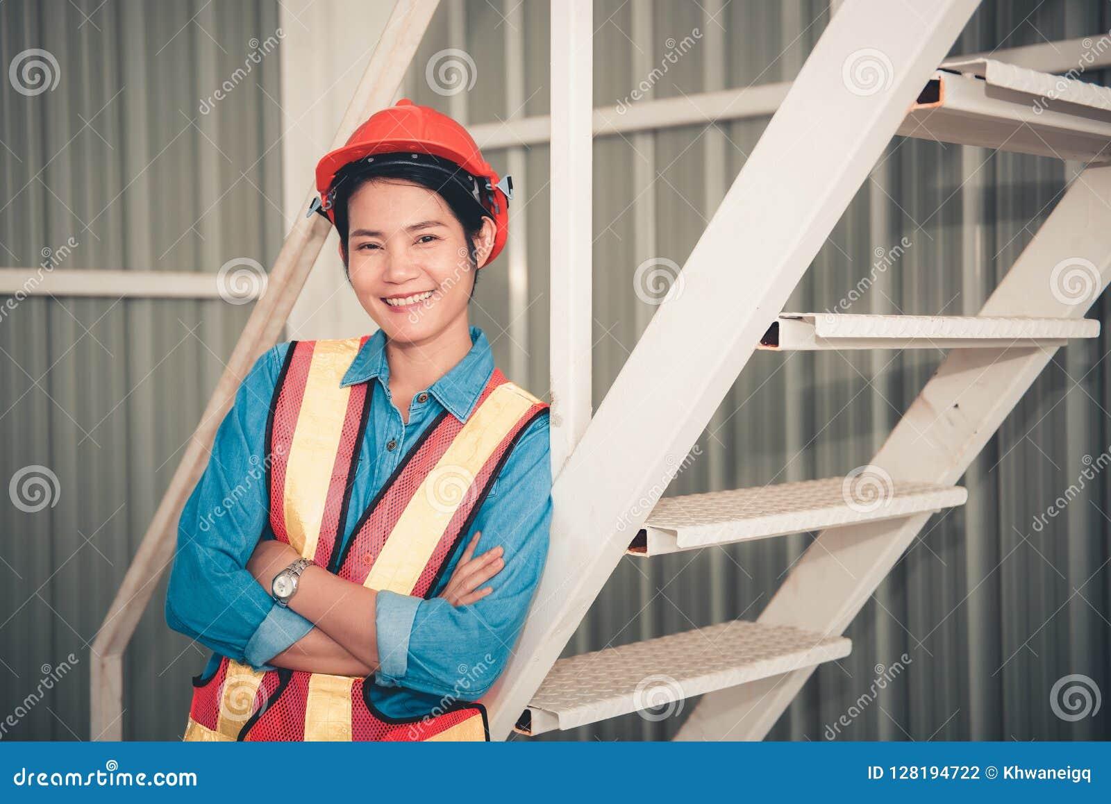 Retrato de una mujer del ingeniero que presenta los brazos cruzados confiados y