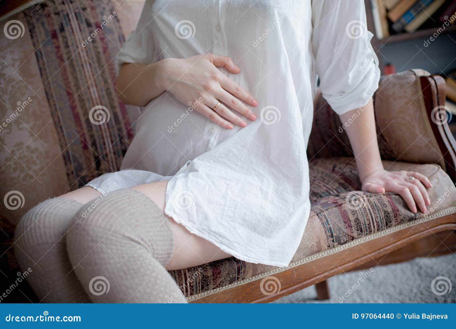 5c91c9a71 Retrato de una mujer embarazada joven en la camisa blanca en el estudio en  una silla