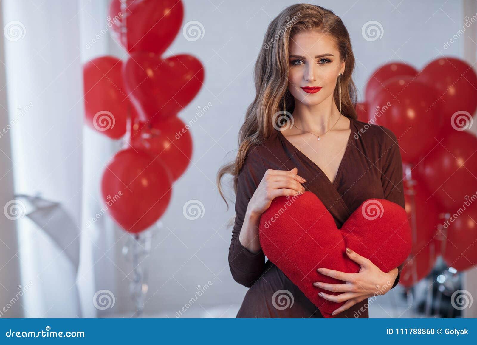 Retrato de una mujer hermosa en día del ` s de la tarjeta del día de San Valentín en un fondo de los balones de aire rojos
