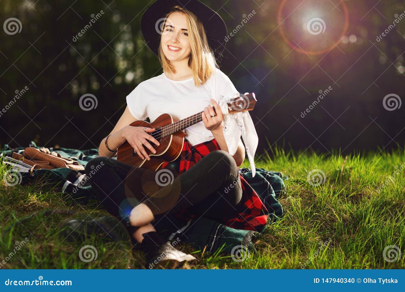 Retrato de una mujer hermosa joven en un sombrero negro Muchacha que se sienta en la hierba y que toca la guitarra