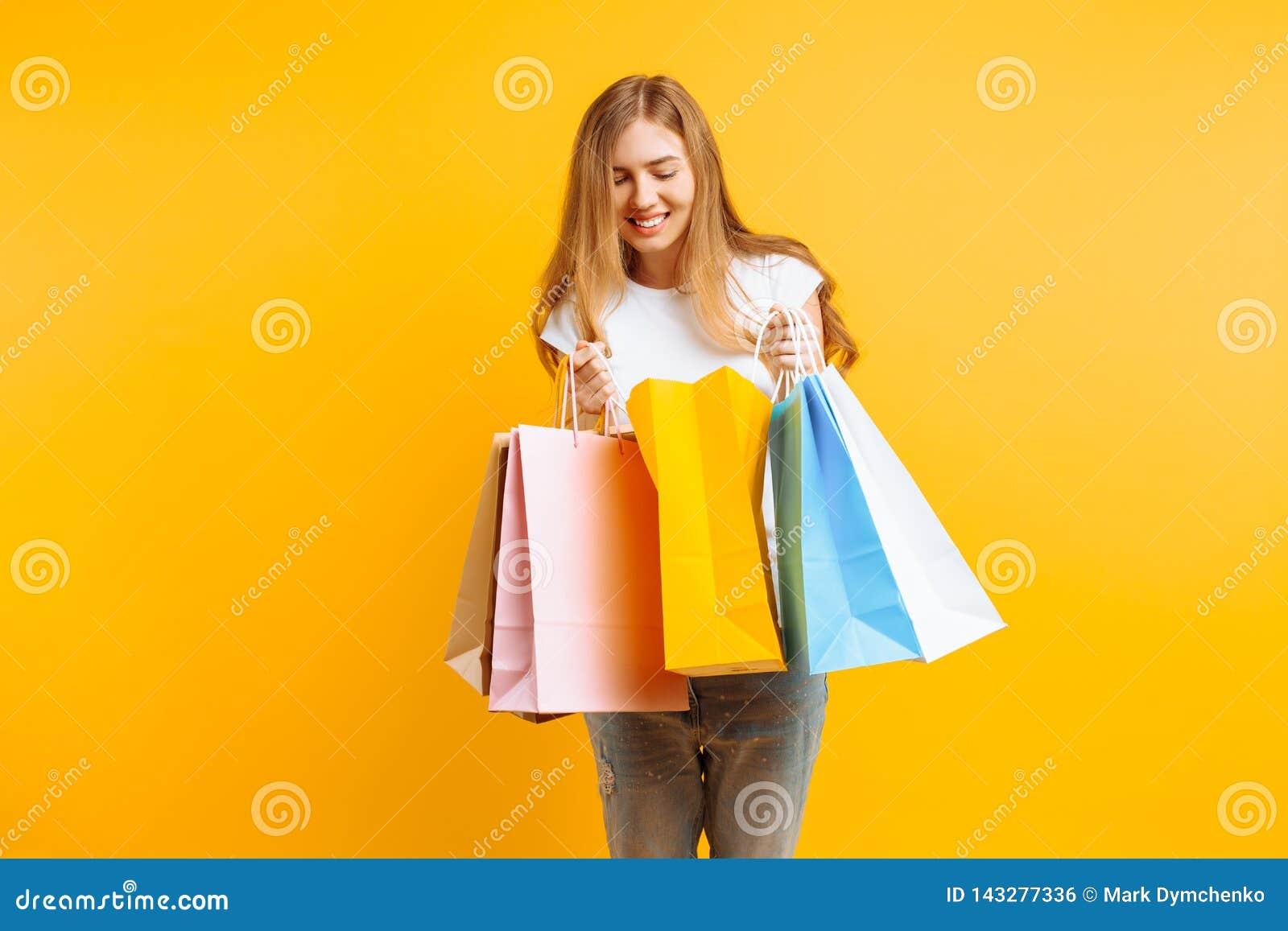 Retrato de una mujer joven curiosa, después de buenas compras, mirando dentro del bolso, aislado en un fondo amarillo