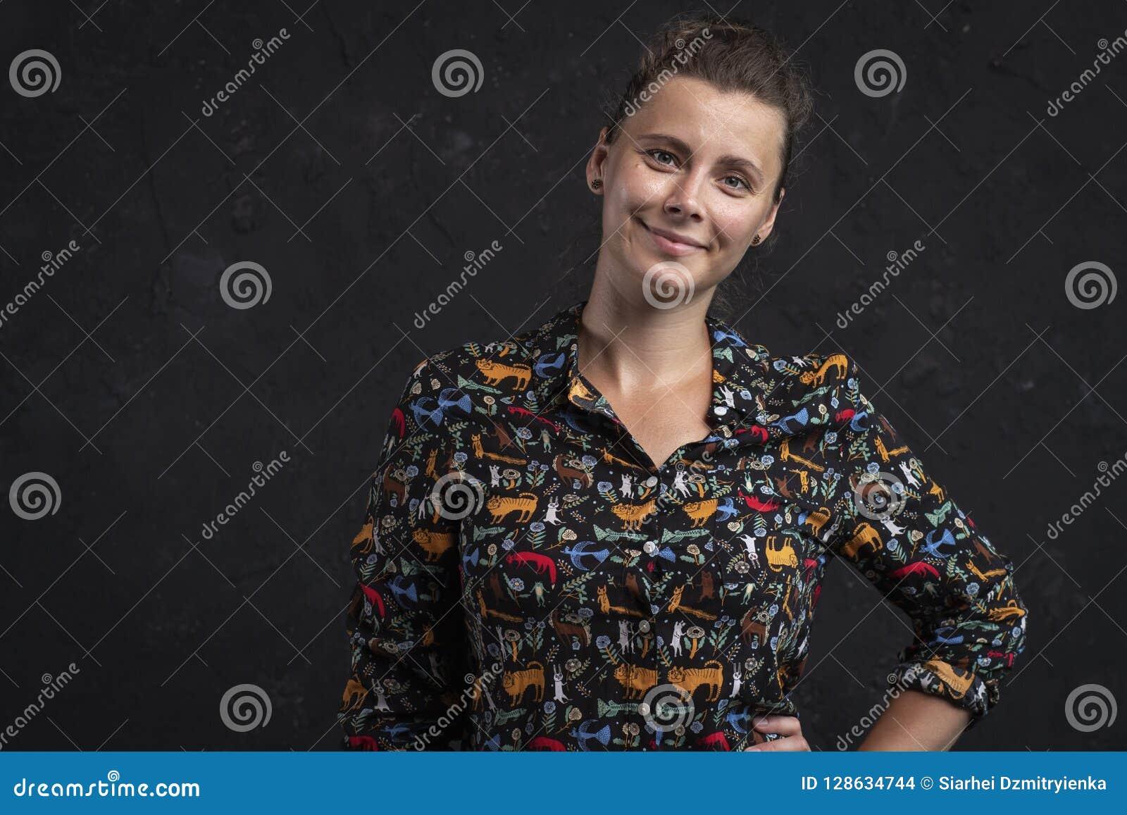Retrato de una mujer joven en un fondo negro Muchacha natural atractiva en una camisa negra Muchacha del tiro del estudio que mir