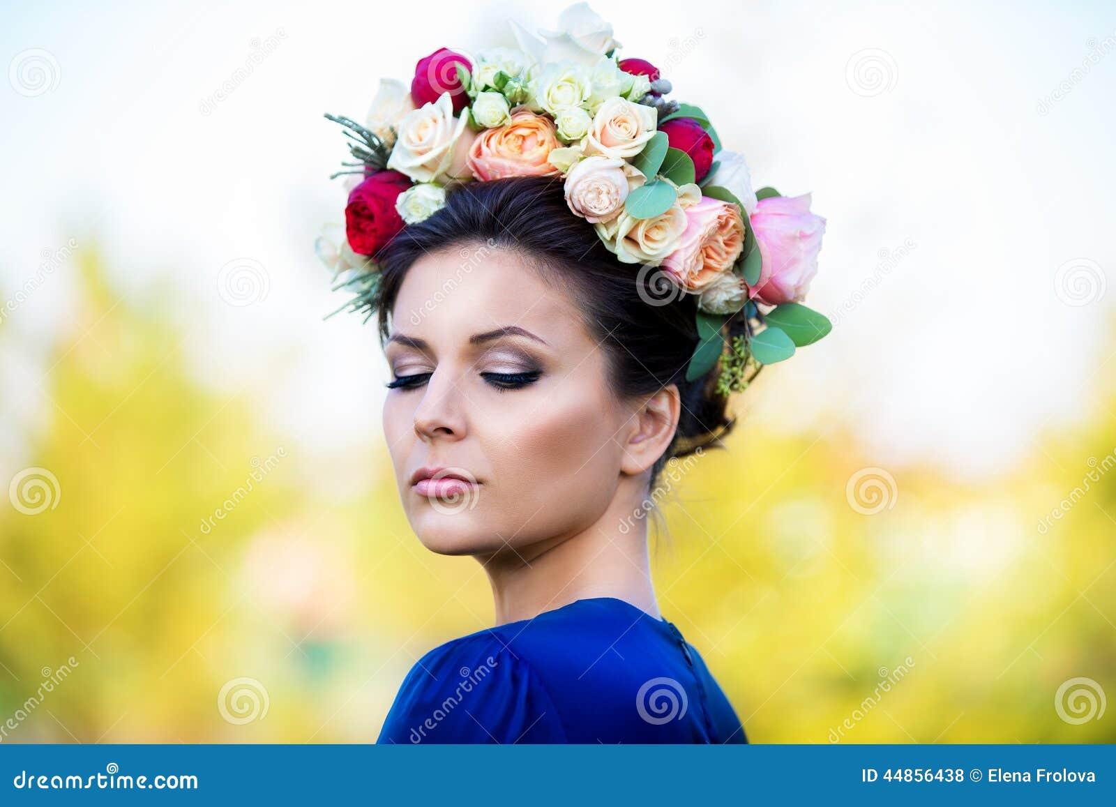 Retrato de una mujer joven hermosa en una guirnalda de rosas, outdoo