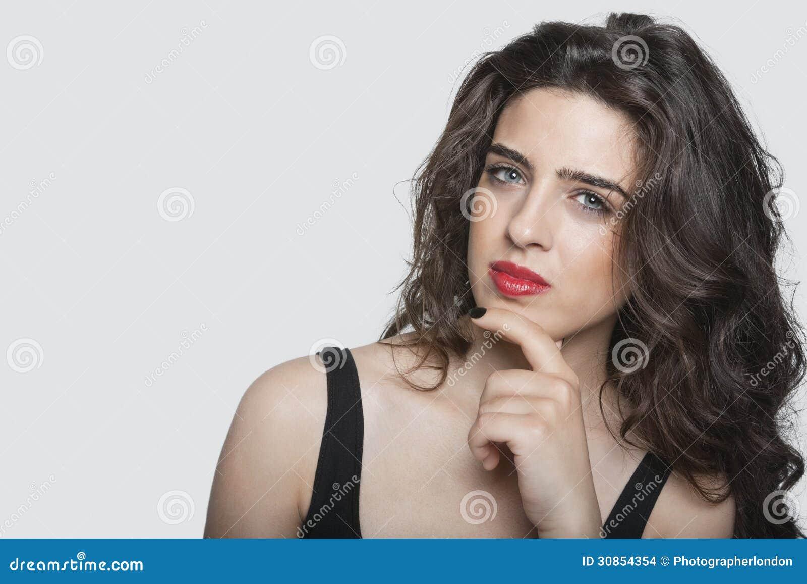 Retrato de una mujer joven pensativa con la mano en la barbilla sobre fondo gris