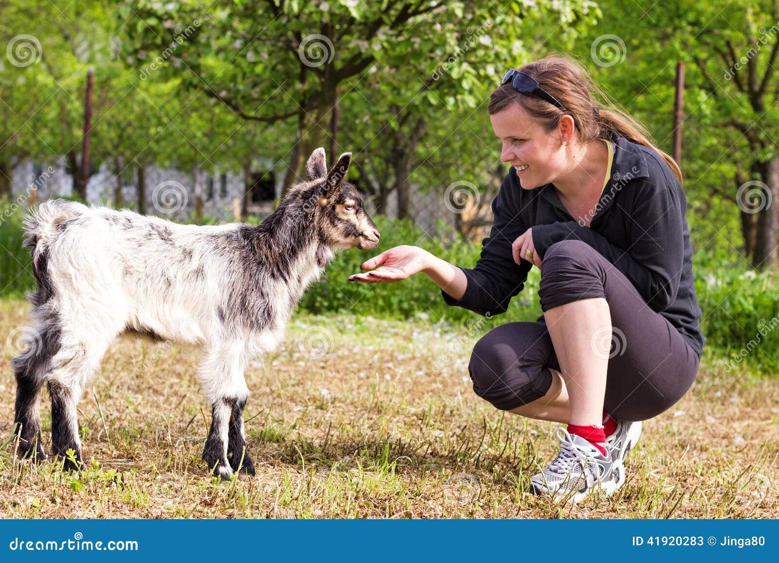 Retrato de una mujer joven que juega la cabra del bebé