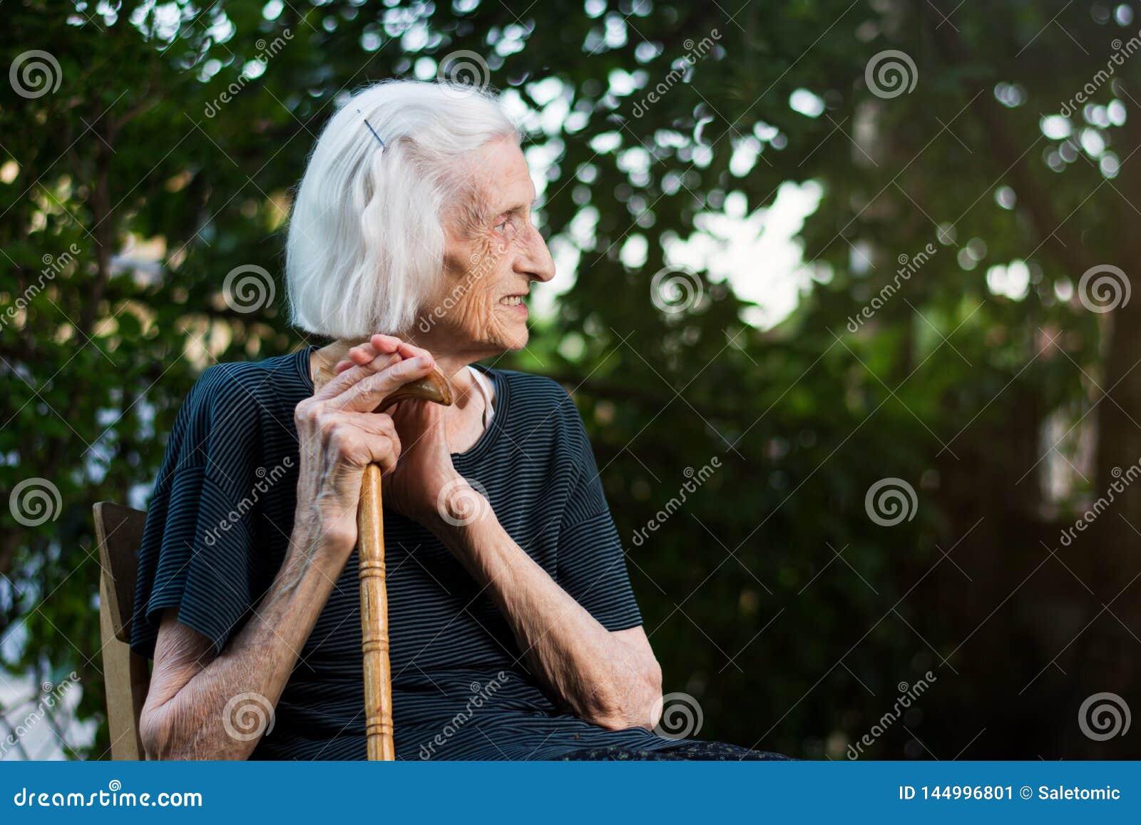 Retrato de una mujer mayor con un bastón que camina
