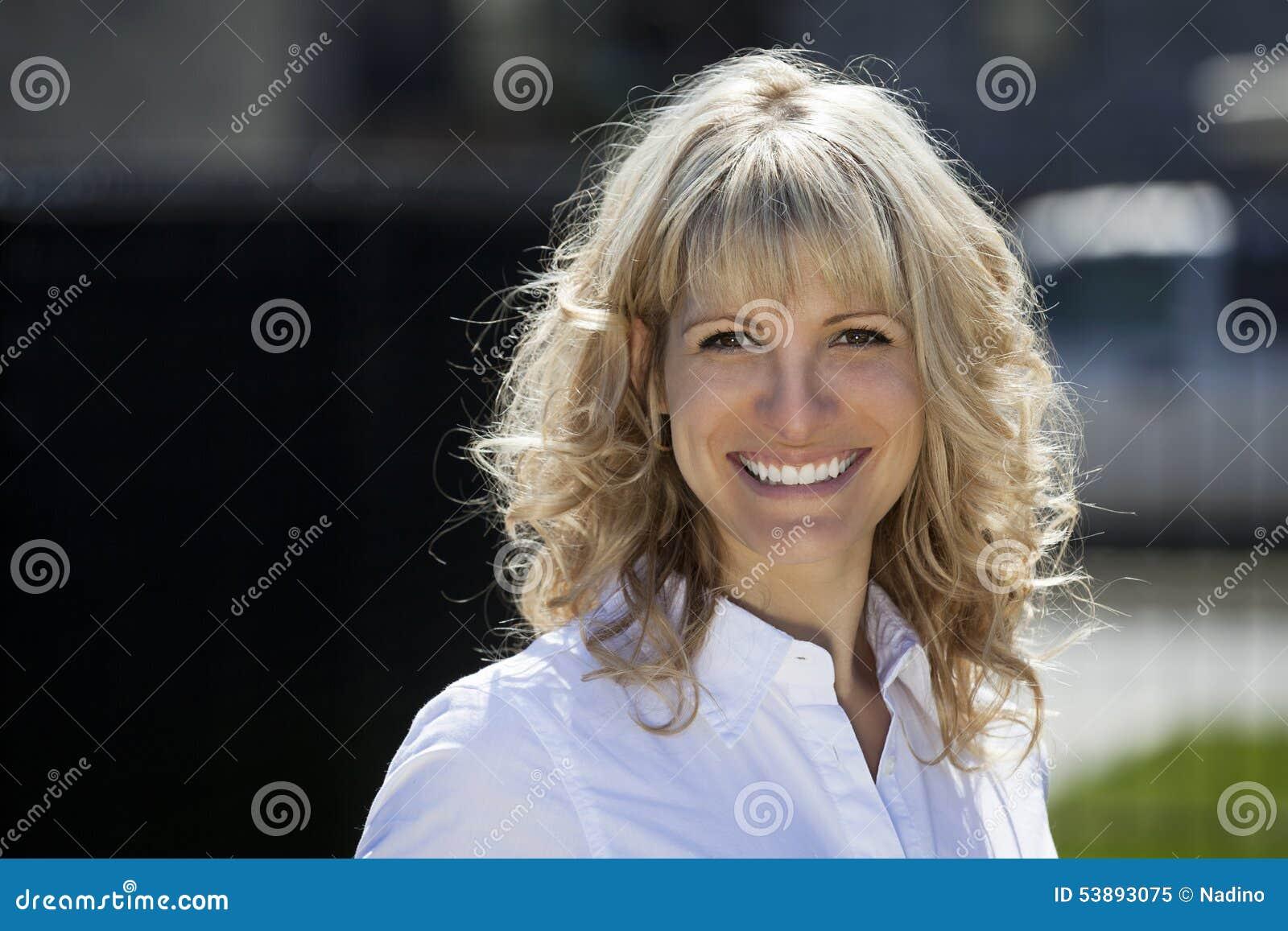 Retrato de una mujer rubia feliz afuera
