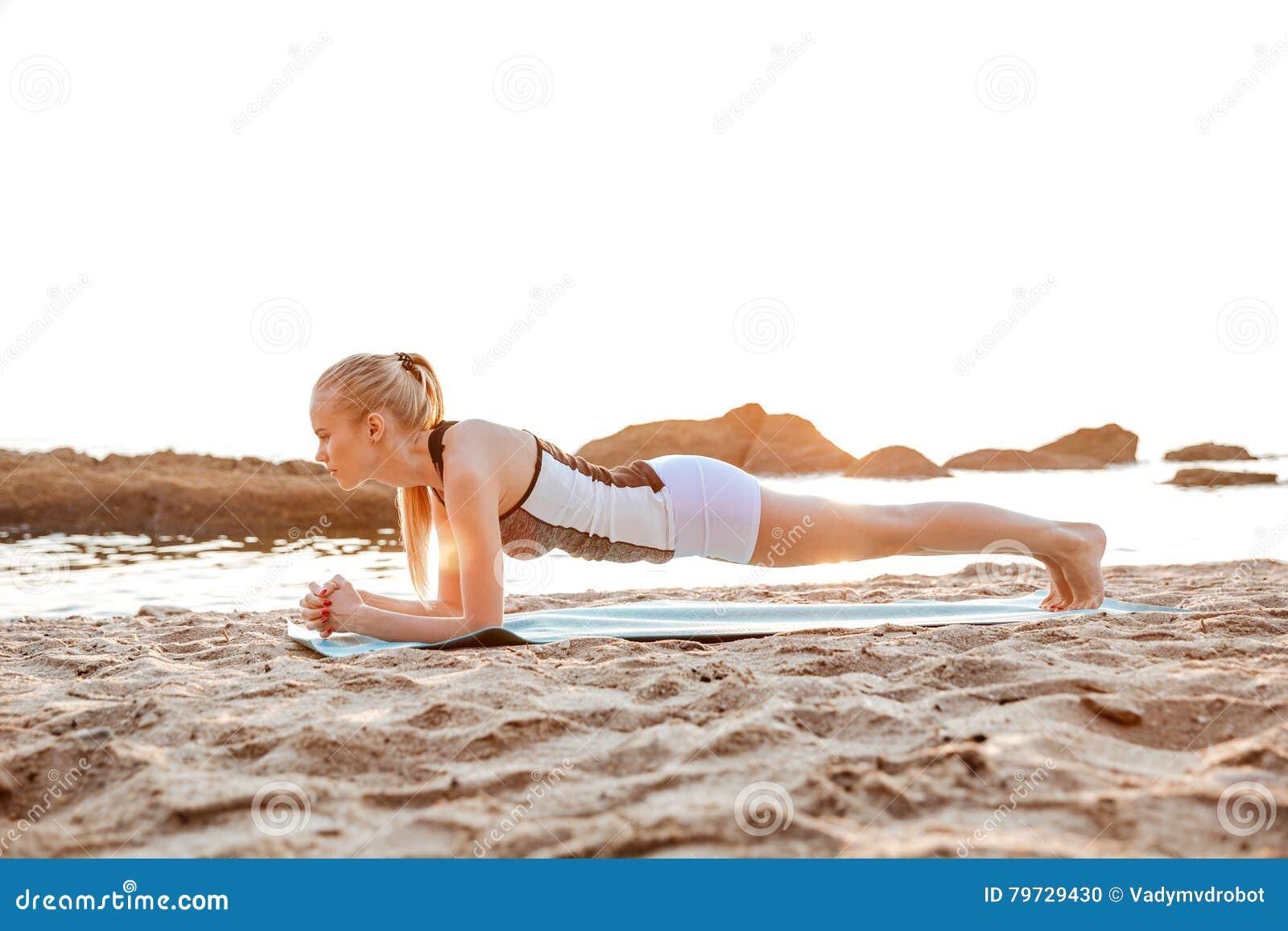 Retrato de una mujer rubia que hace el tablaje en la estera de la yoga