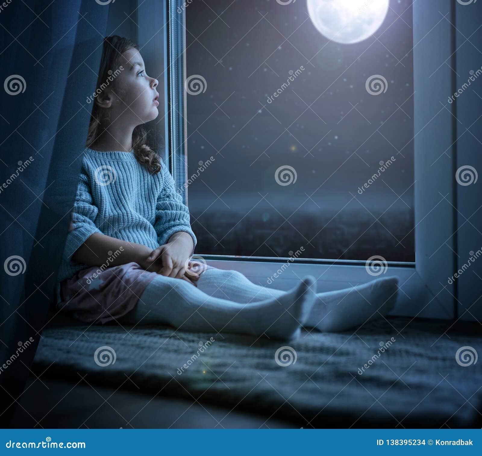 Retrato de una niña linda que mira la luna de la noche