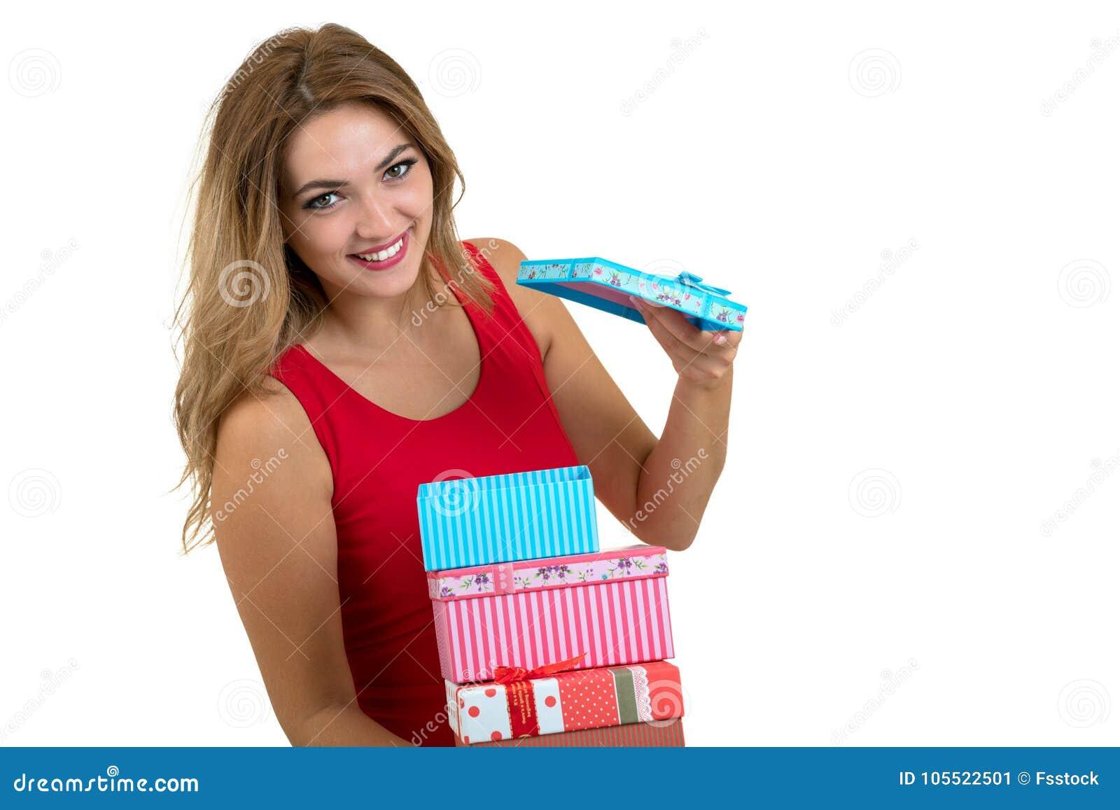 Retrato de una pila bonita sonriente de la tenencia de la muchacha de cajas de regalo aisladas sobre el fondo blanco