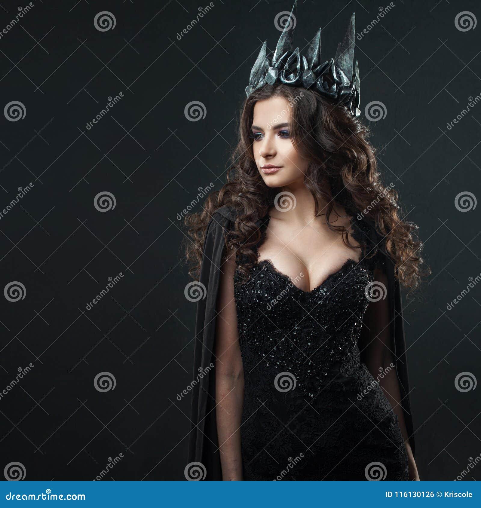 Retrato de una princesa gótica Mujer morena joven hermosa en corona del metal y capa negra