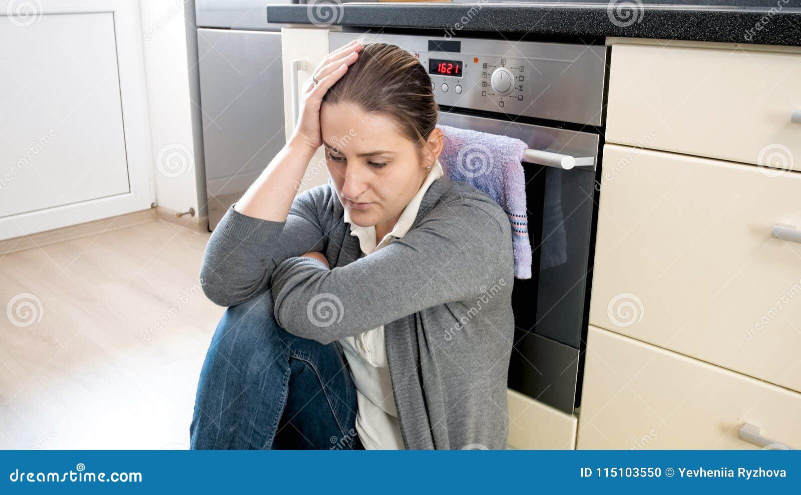 Retrato del ama de casa joven que sufre de la depresión que se sienta en piso en la cocina