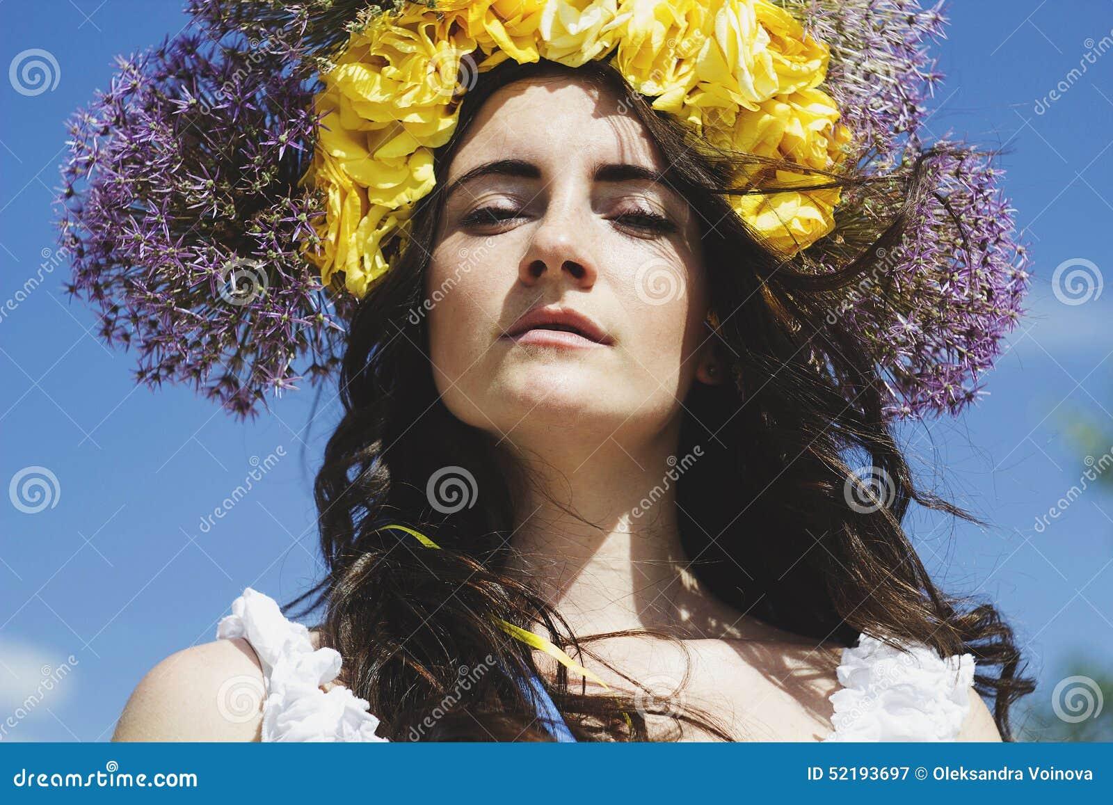 Retrato del anillo hermoso joven de la mujer de flores en la cabeza