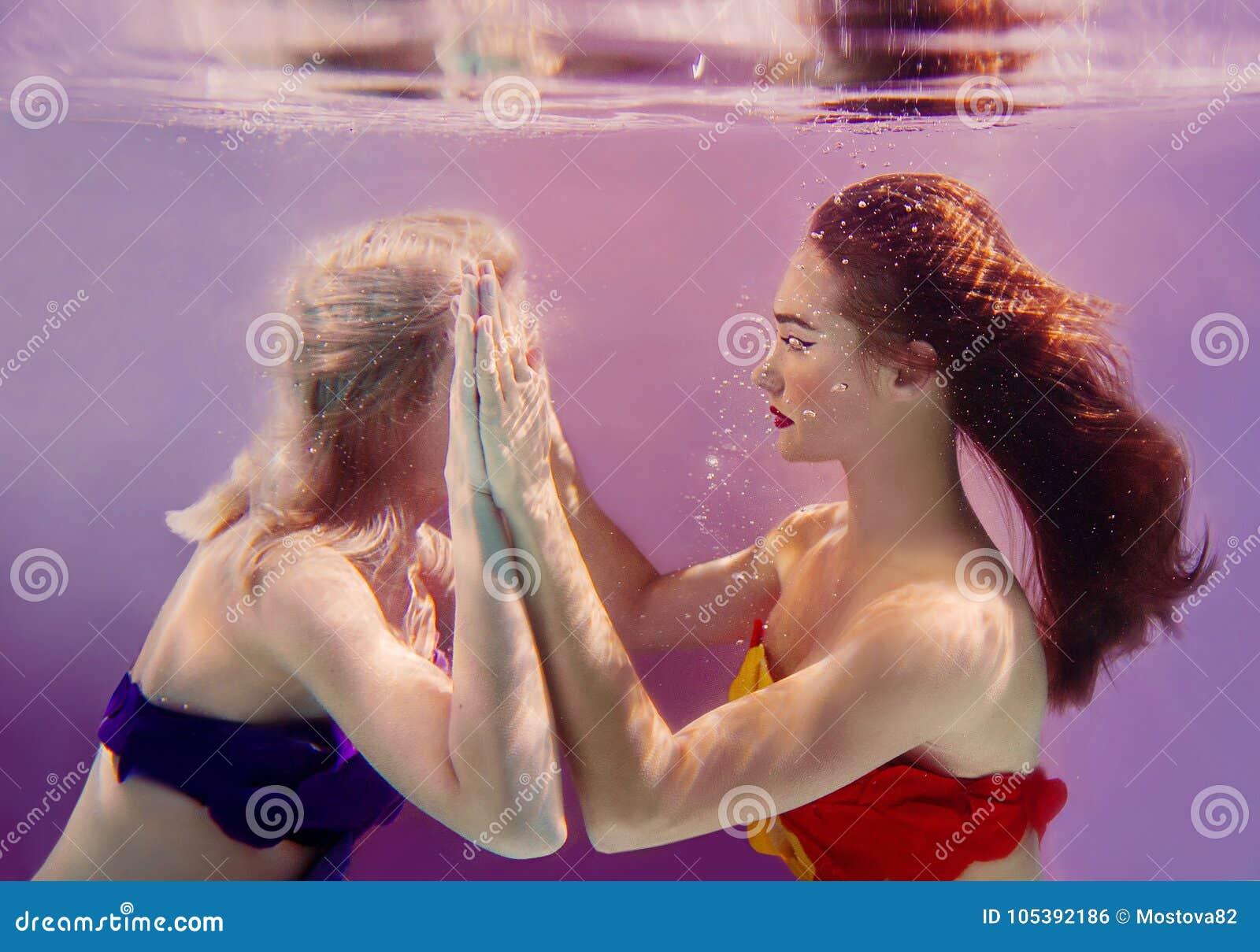 Retrato del arte de dos muchachas bonitas hermosas que se detienen manos subacuático