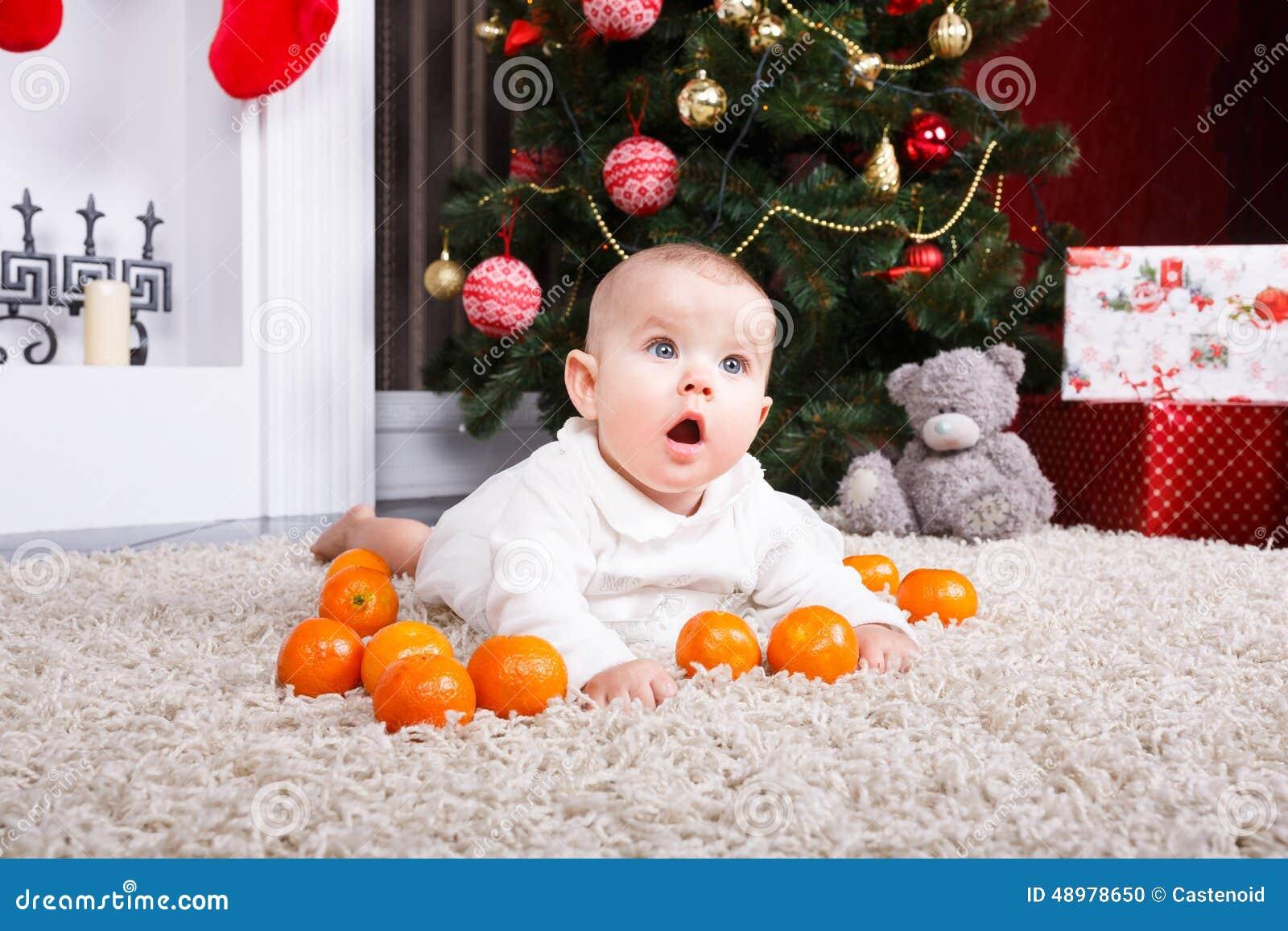 Retrato del bebé con la mandarina