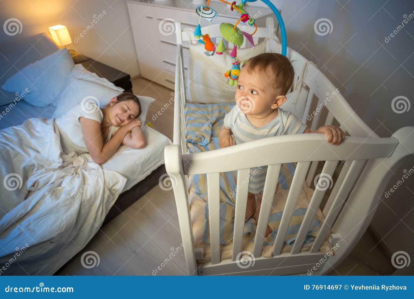 Retrato del bebé que se coloca en pesebre y que mira el th cansado de la madre