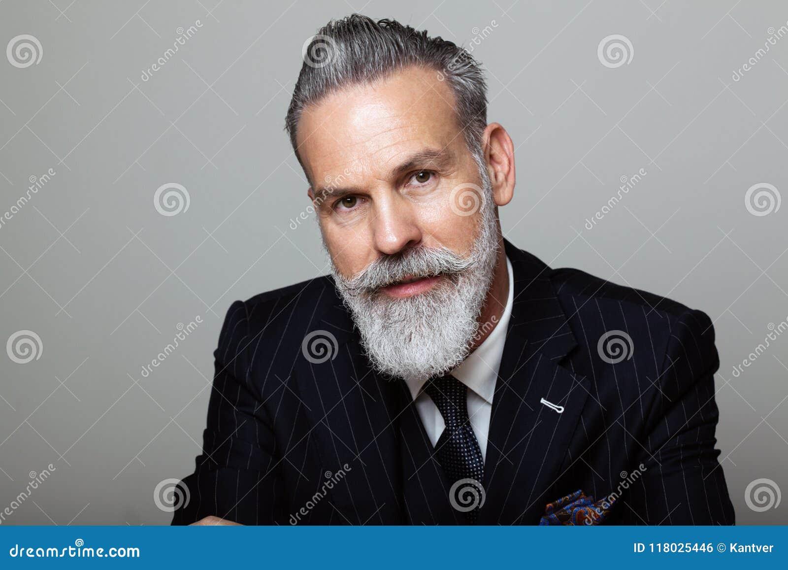 Retrato del caballero barbudo atractivo que lleva el traje de moda sobre fondo gris vacío Tiro del estudio, concepto de la moda