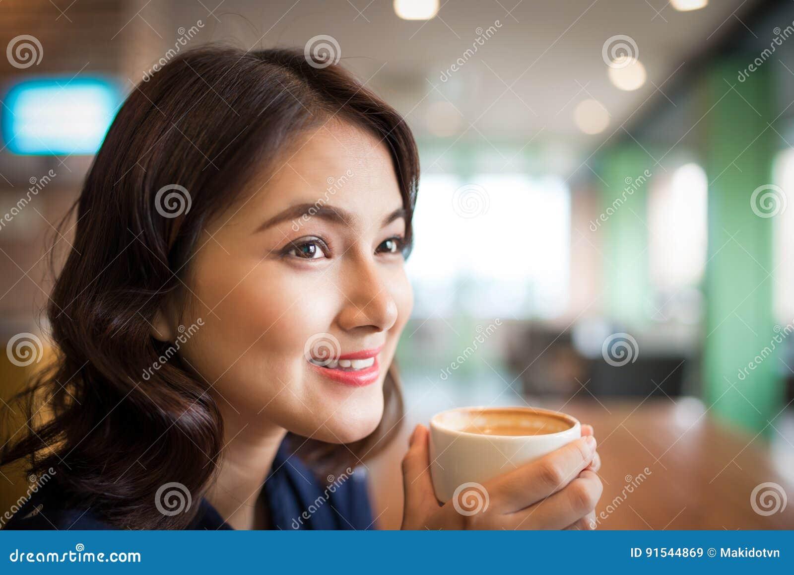 Retrato del café de consumición de la mujer asiática joven atractiva